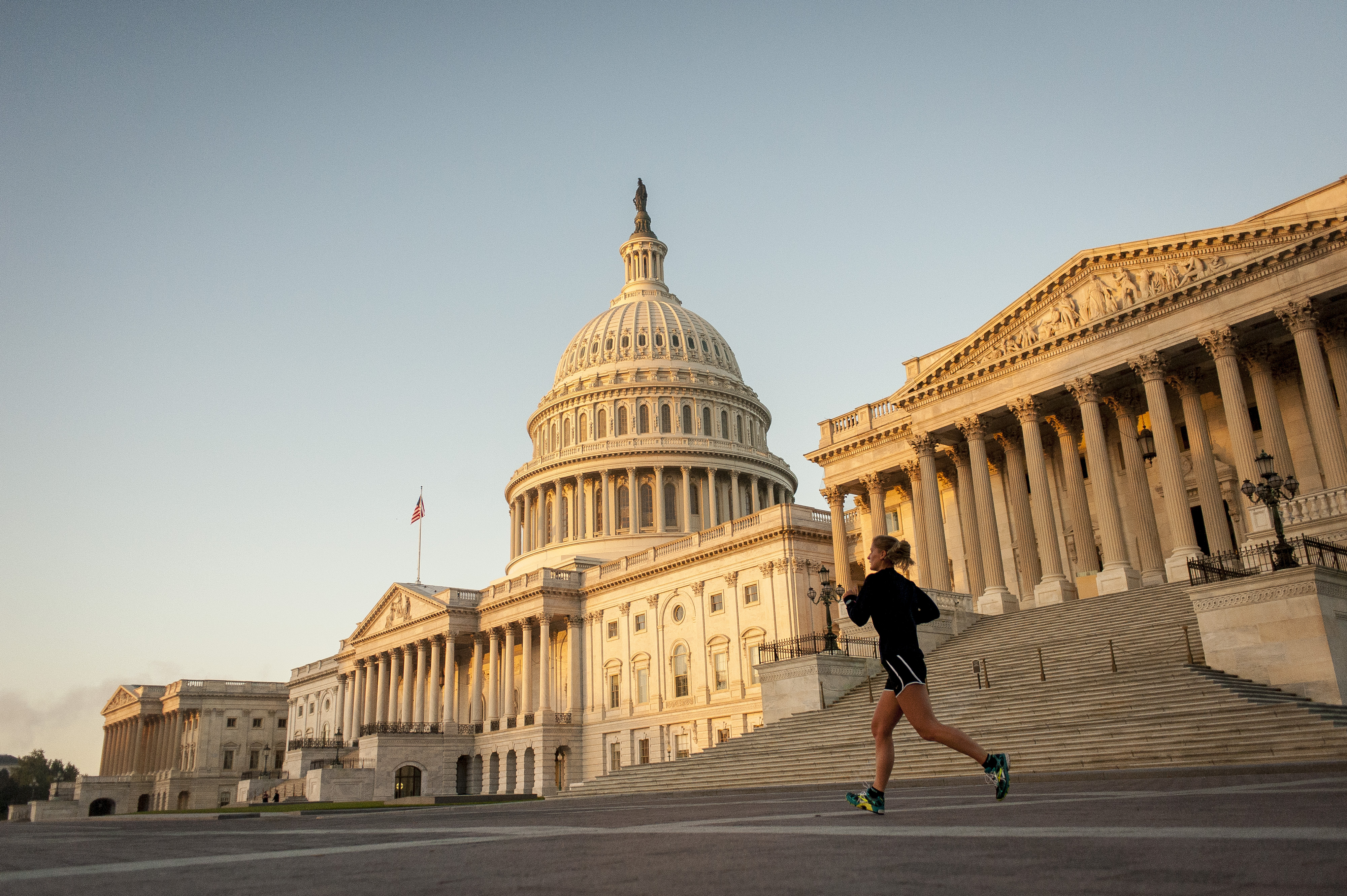 A jogger runs past the United States Capitol building at sunrise in Washington, D.C., U.S., on Tuesday, Oct. 15, 2013.