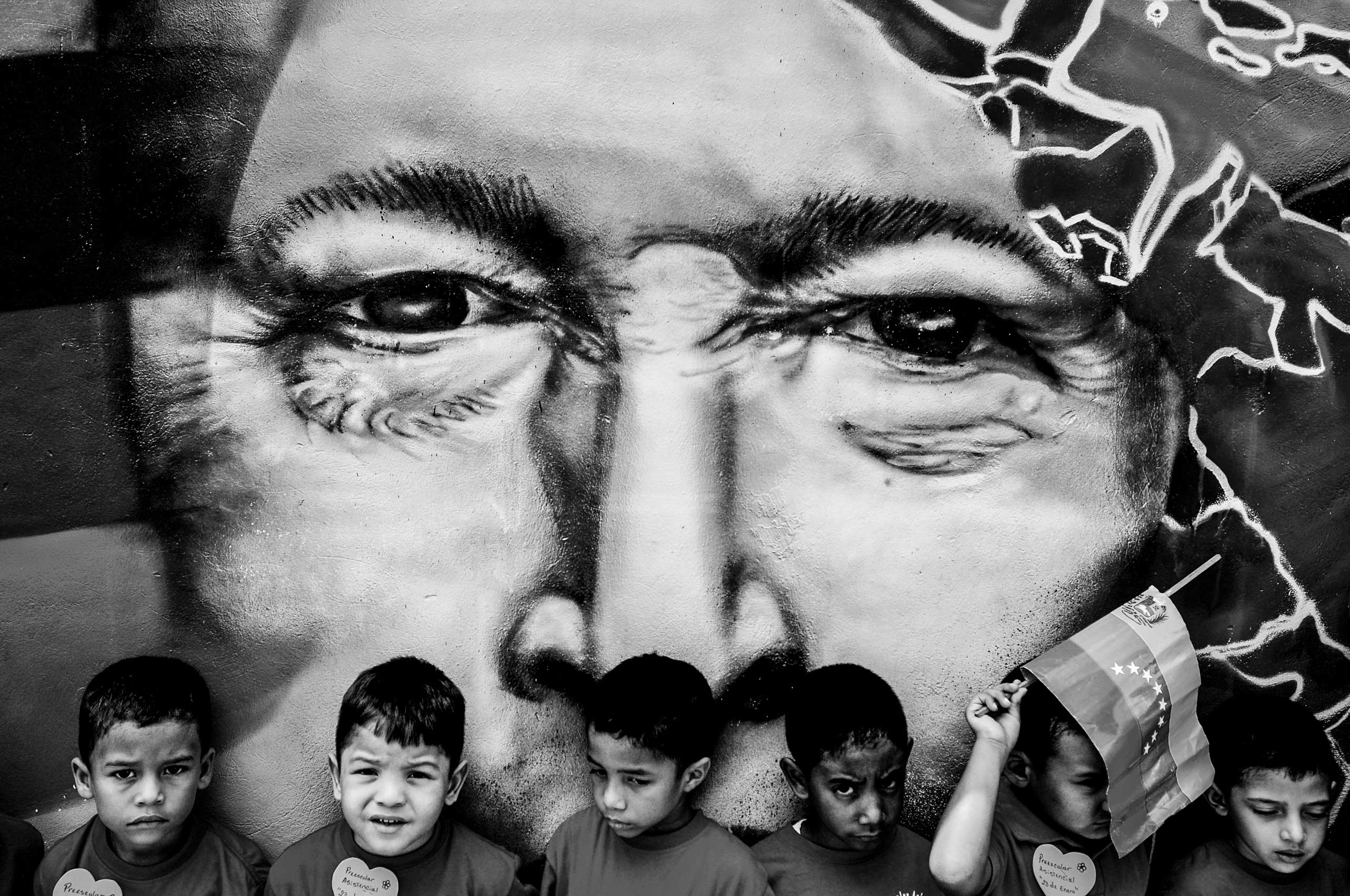 A group of children in front of graffiti of Hugo Chávez, during a school trip to the location of the former president's remains. Caracas, May 2013.