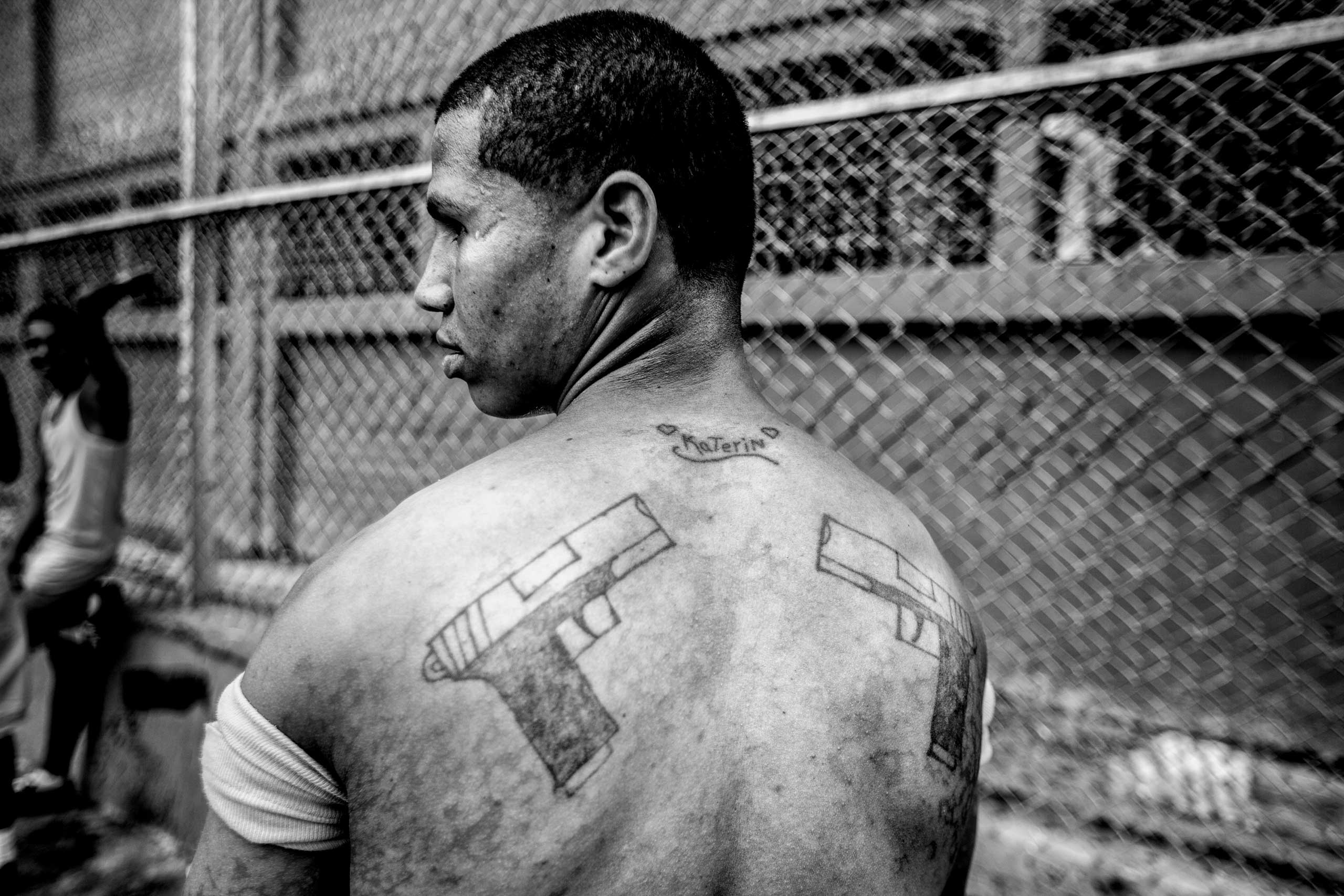 An inmate poses for a photo showing his tattoos dedicated to a girl named Katerin. Guatire, outside Caracas, April 2014.