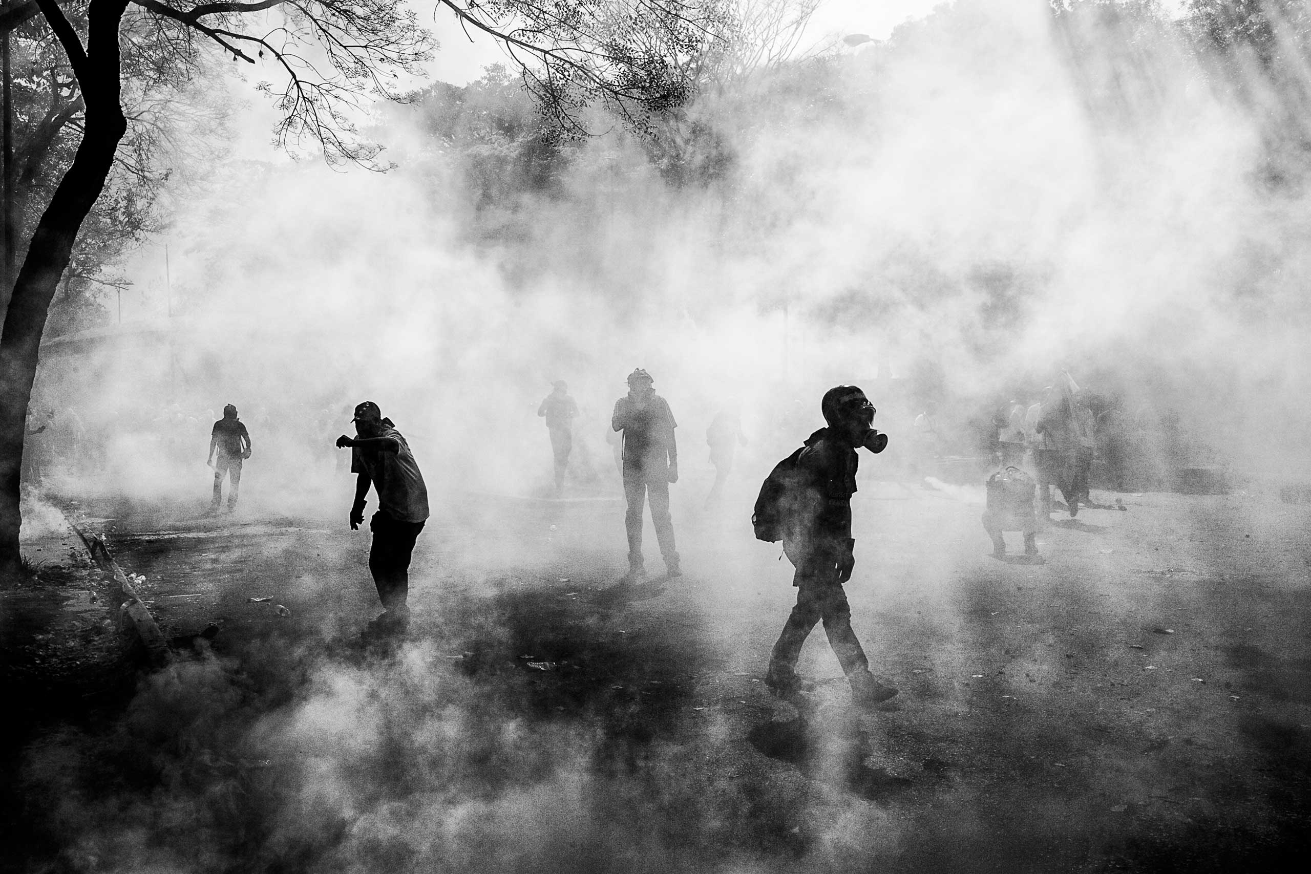 Demonstrators walk through a cloud of tear gas fired by the Bolivarian National Guard [?] during clashes between antigovernment protestors and government security forces. Caracas, March 2014.