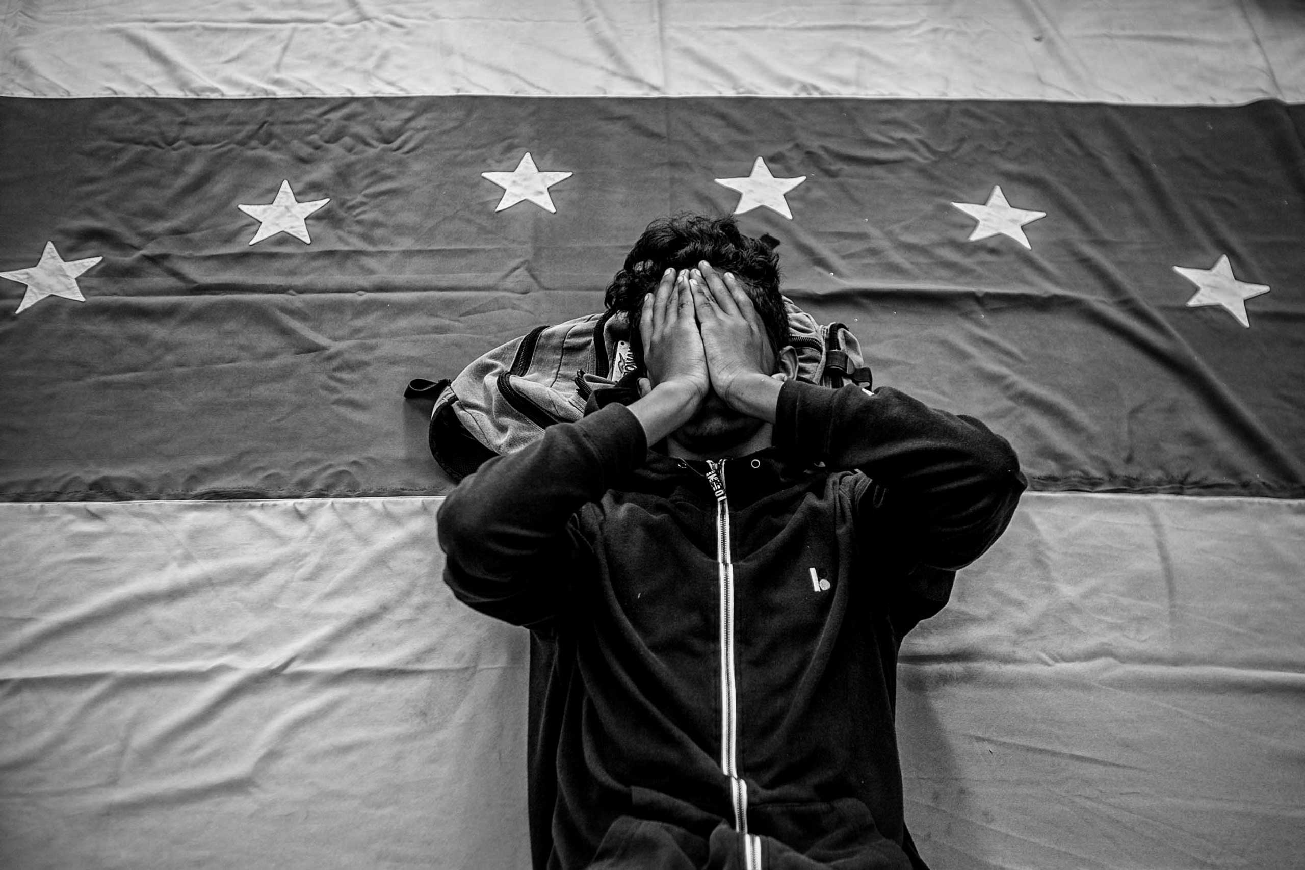 A man covers his face while lying on a Venezuelan flag during a demonstration to demand the release of Metropolitan Mayor Antonio Ledezma. The mayor was arrested under the charges of conspiracy against Venezuela's President Nicolás Maduro. Caracas, February 2015.