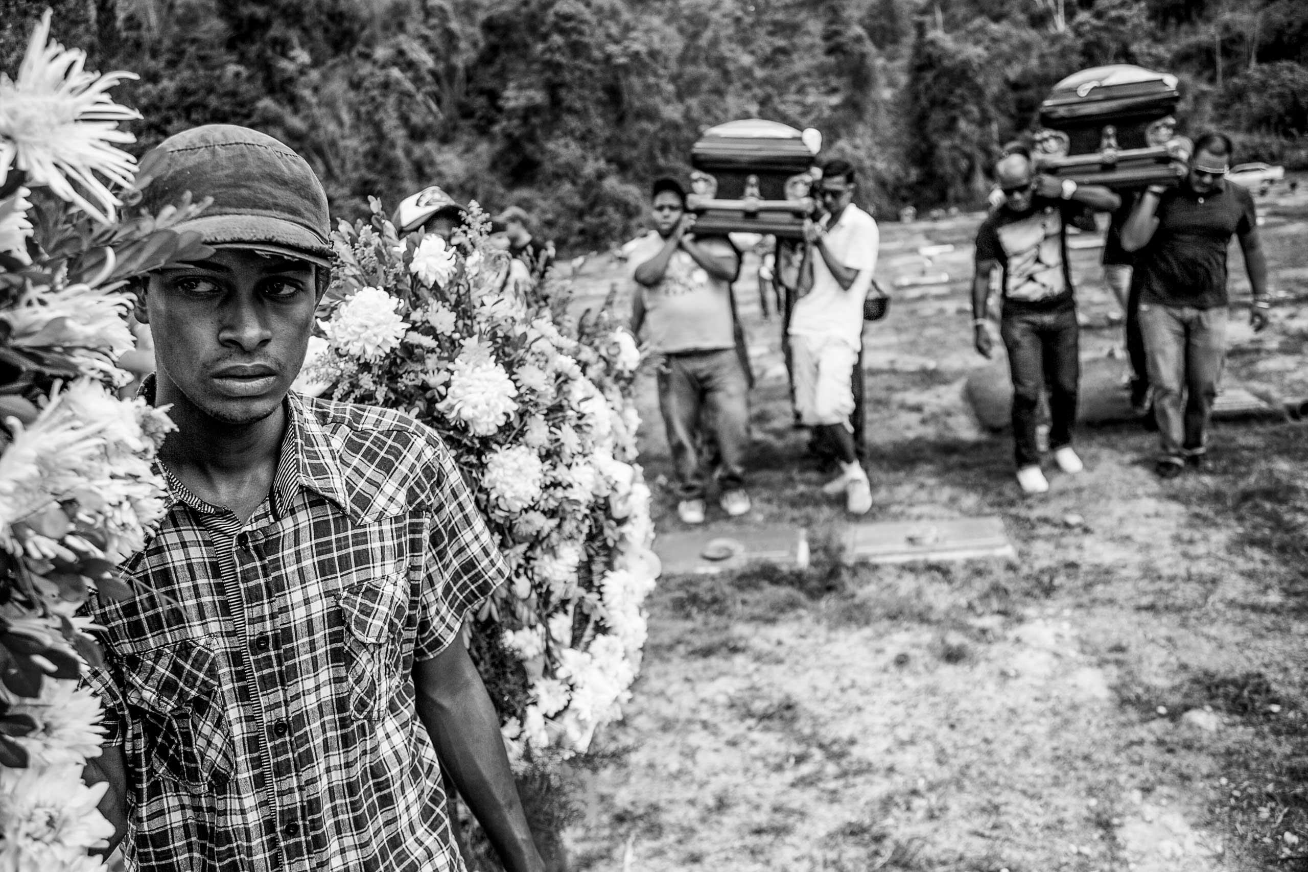 A relative of the Balza brothers carries an arrangement of flowers during their burial in the east cemetery of Caracas. The homicide in which the Balza brothers were killed—inside a hospital where had gone after one of them had been shot during a gang fight—adds to the statistics of 24,000 murders per year. July 2014.