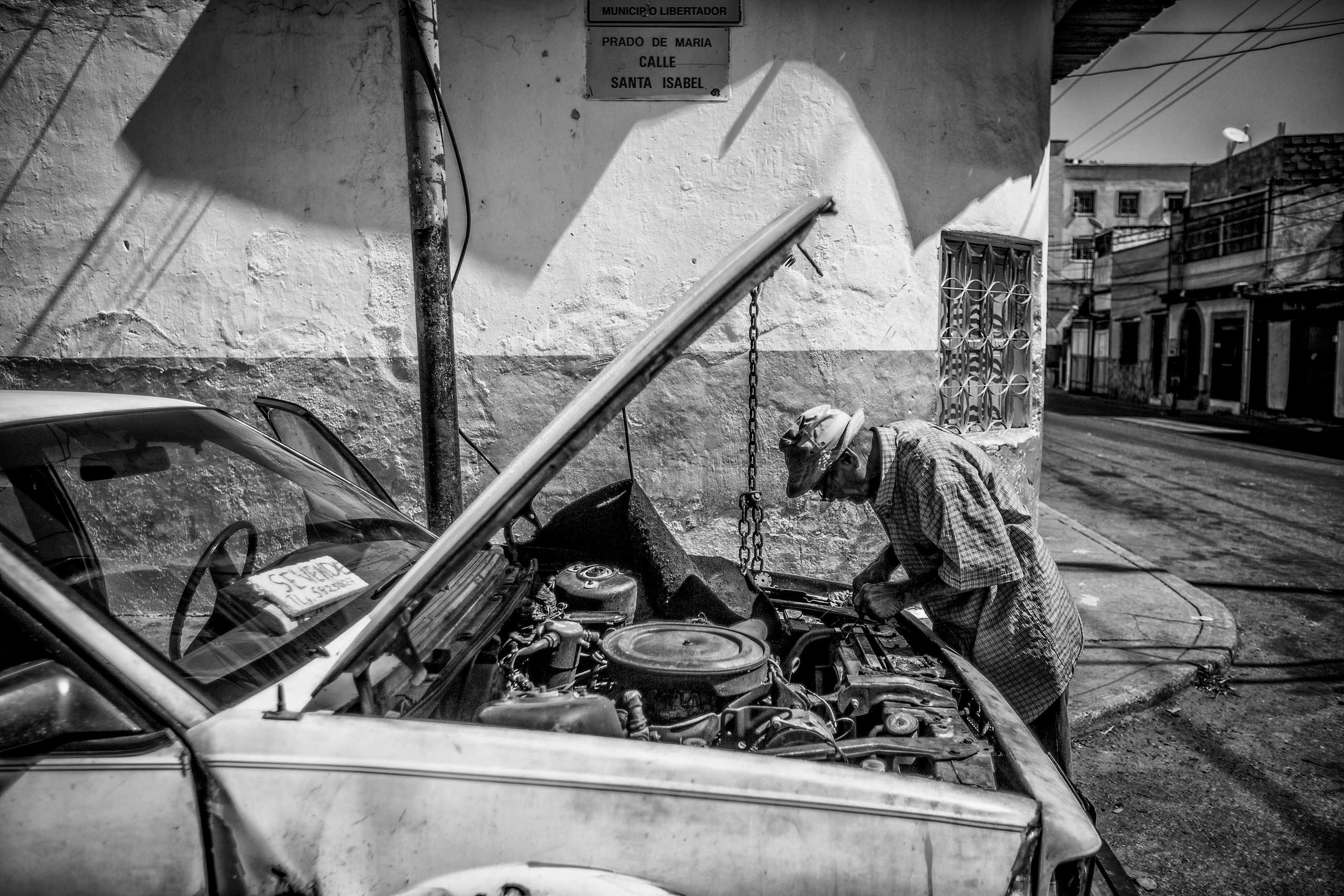 A man repairs an old car in the neighborhood called  The Cemetery.  The shortage of car parts due to the economic crisis has made repairs too expensive. Caracas, January 2015.