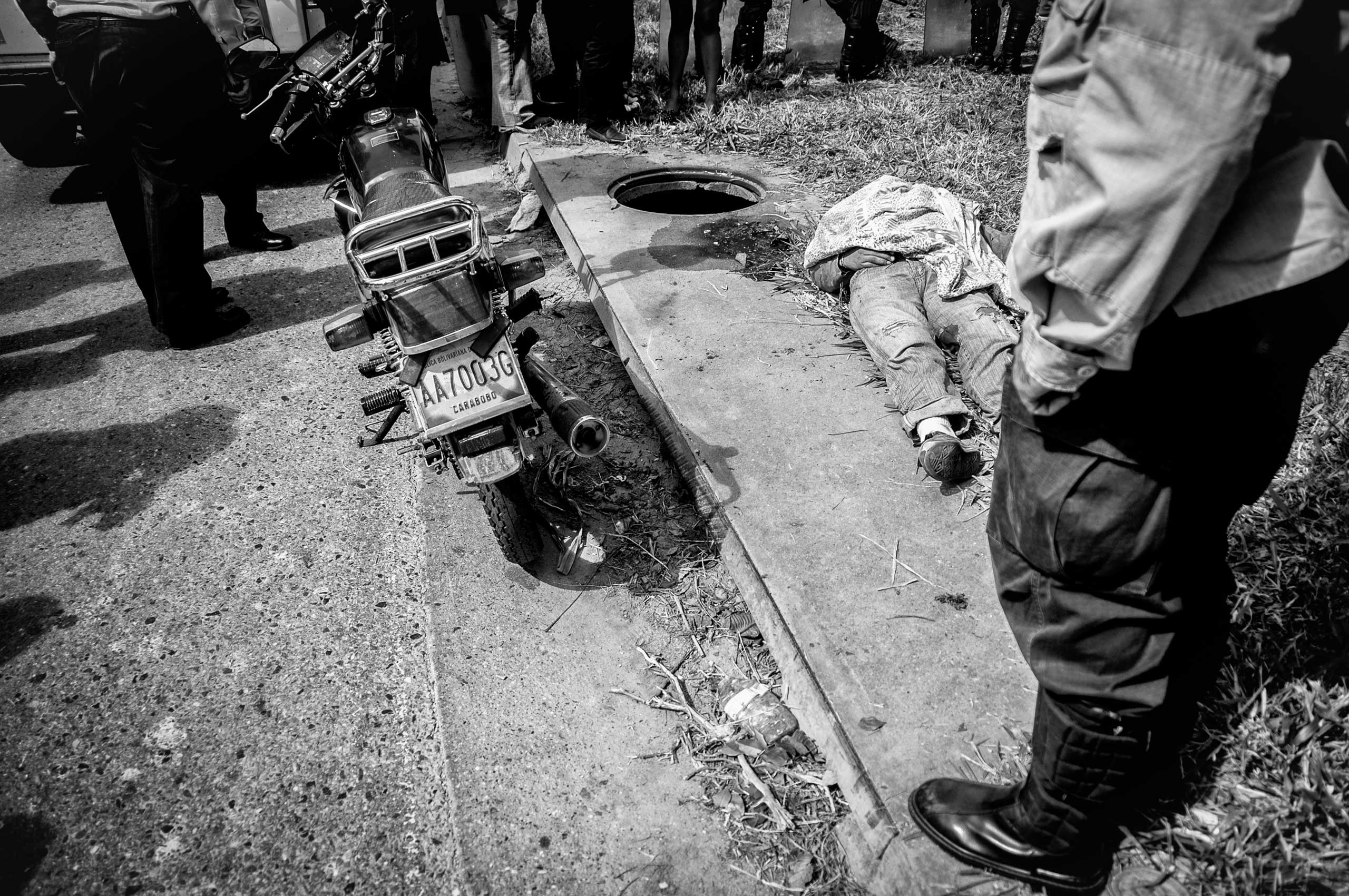 Luis Alfredo Torres, a motorbike taxi rider, was executed on Caracas' main highway during an attempted robbery of his bike. The supply shortage of spare parts makes riders the targets of gangs. Caracas, May 2013.