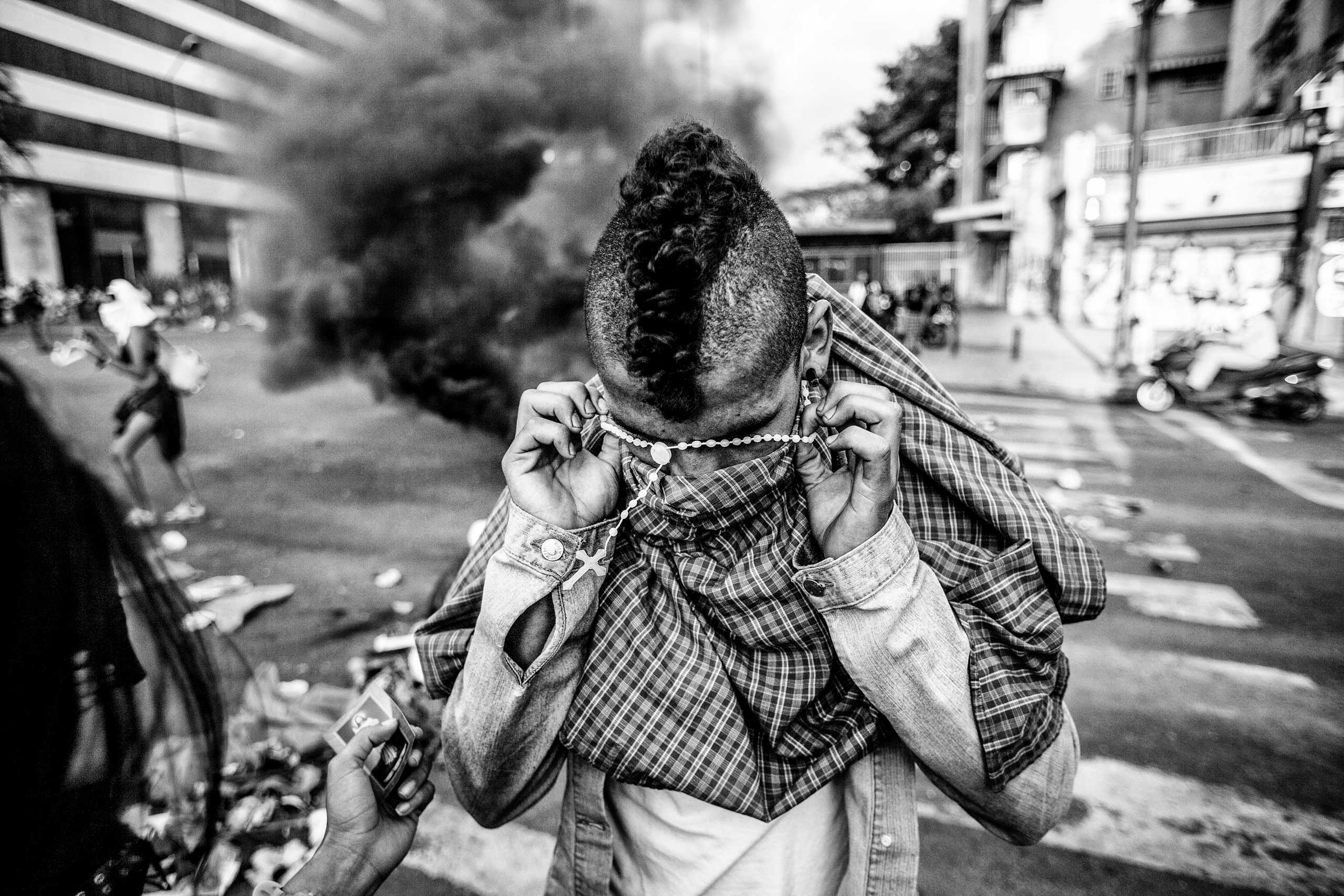 A demonstrator puts a rosary on over his head before clashing with the Bolivarian National Guard during anti-government protests in Caracas. March 2014.
