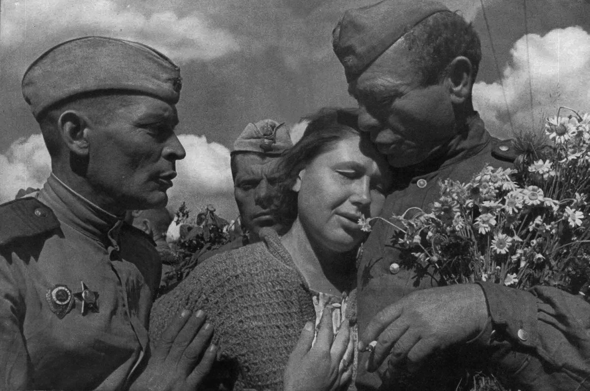 A woman celebrating the defeat of Nazi Germany with members of the victorious Soviet Red Army in 1945. Found in the collection of the Moscow Photo Museum.