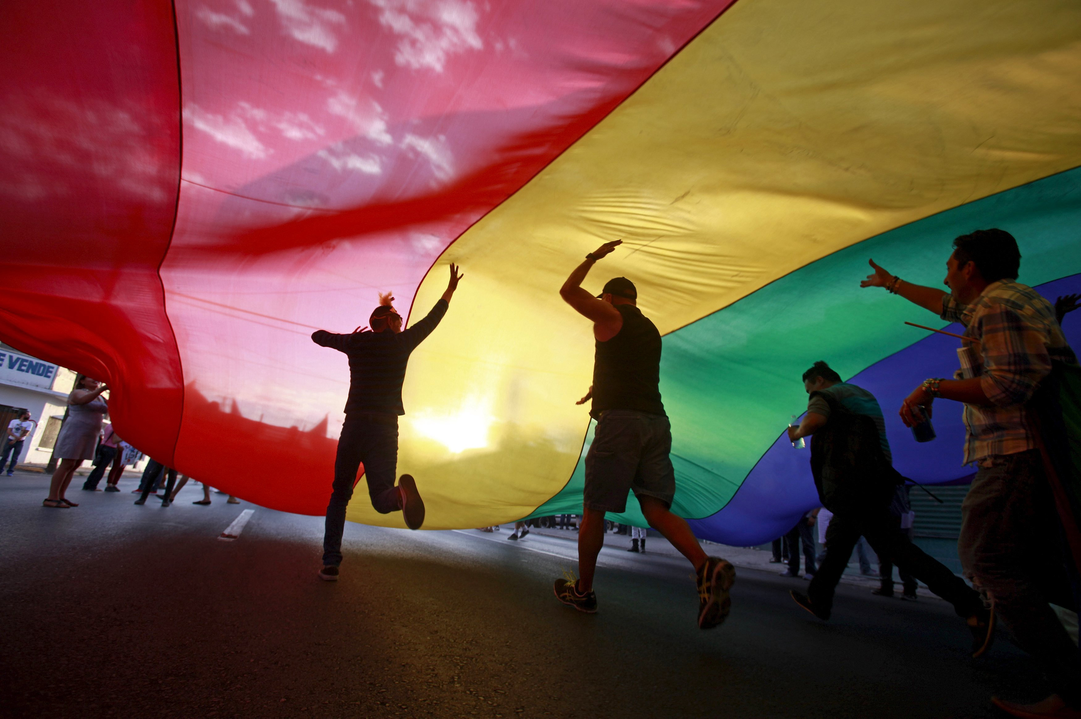 Revelers run under a huge rainbow flag during a Gay Pride parade in Ciudad Juarez, Mexico on June 21, 2015.