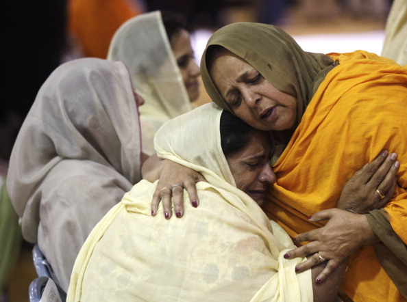 Two women hug as community members in Oak Creek, Wisc., pay respects to the six victims in the mass shooting at the Sikh Temple of Wisconsin on Aug. 10, 2012