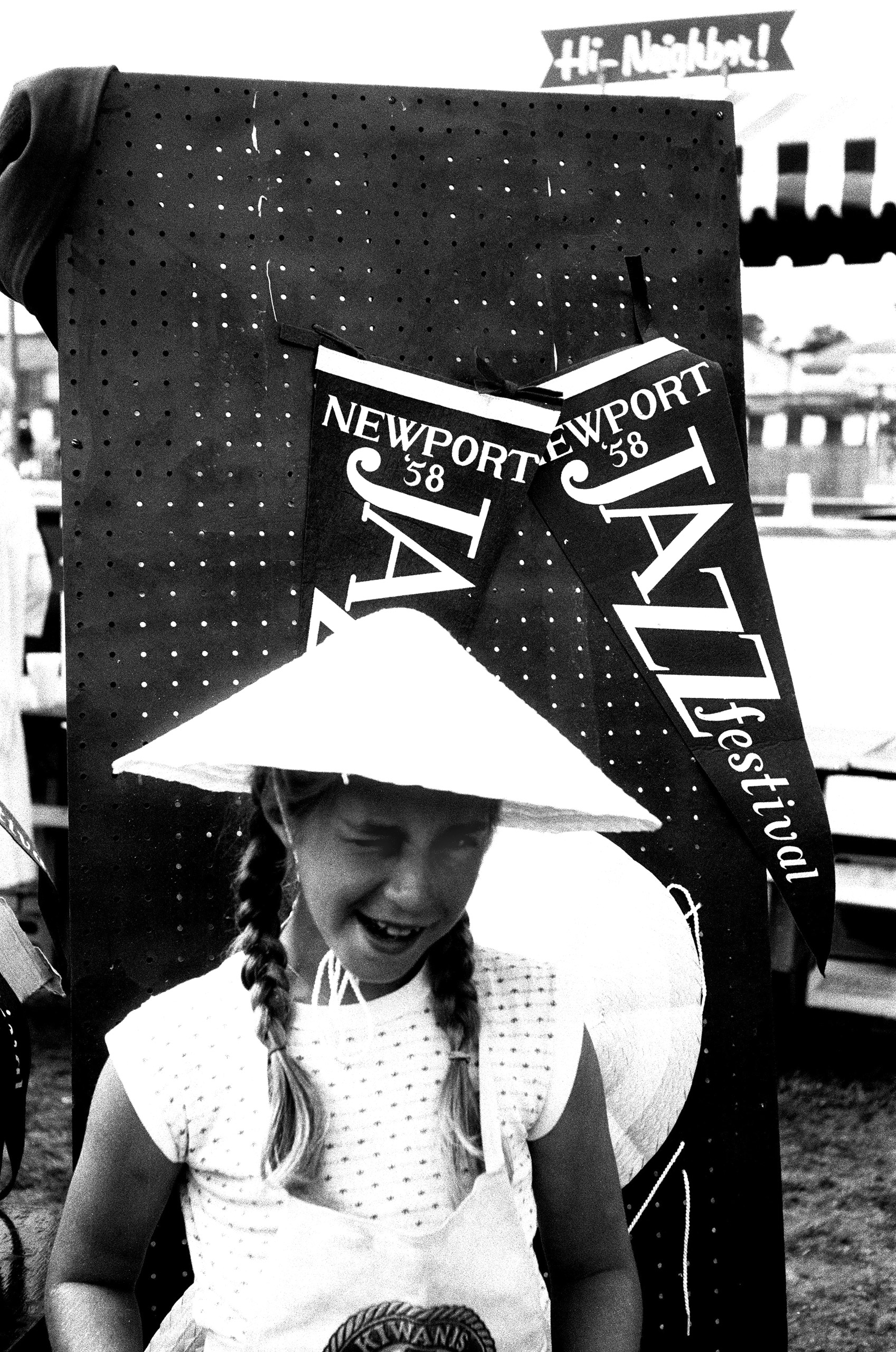 A young fan winks at the camera at the  American Jazz Festival (later renamed the Newport Jazz Festival) in July 1958 in Newport, R.I.