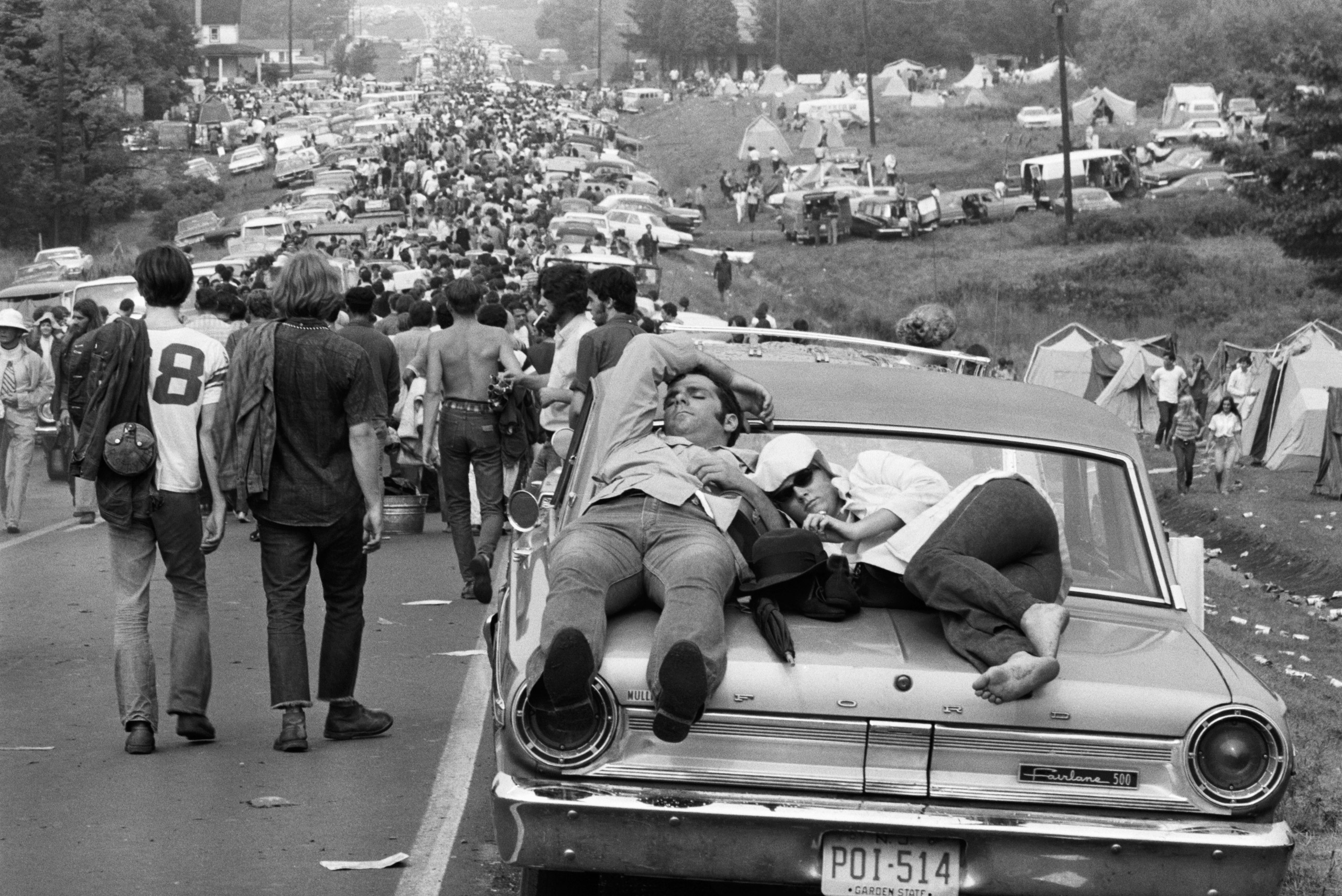 On foot, in cars, atop cars, young people leave the the Woodstock Music Festival.