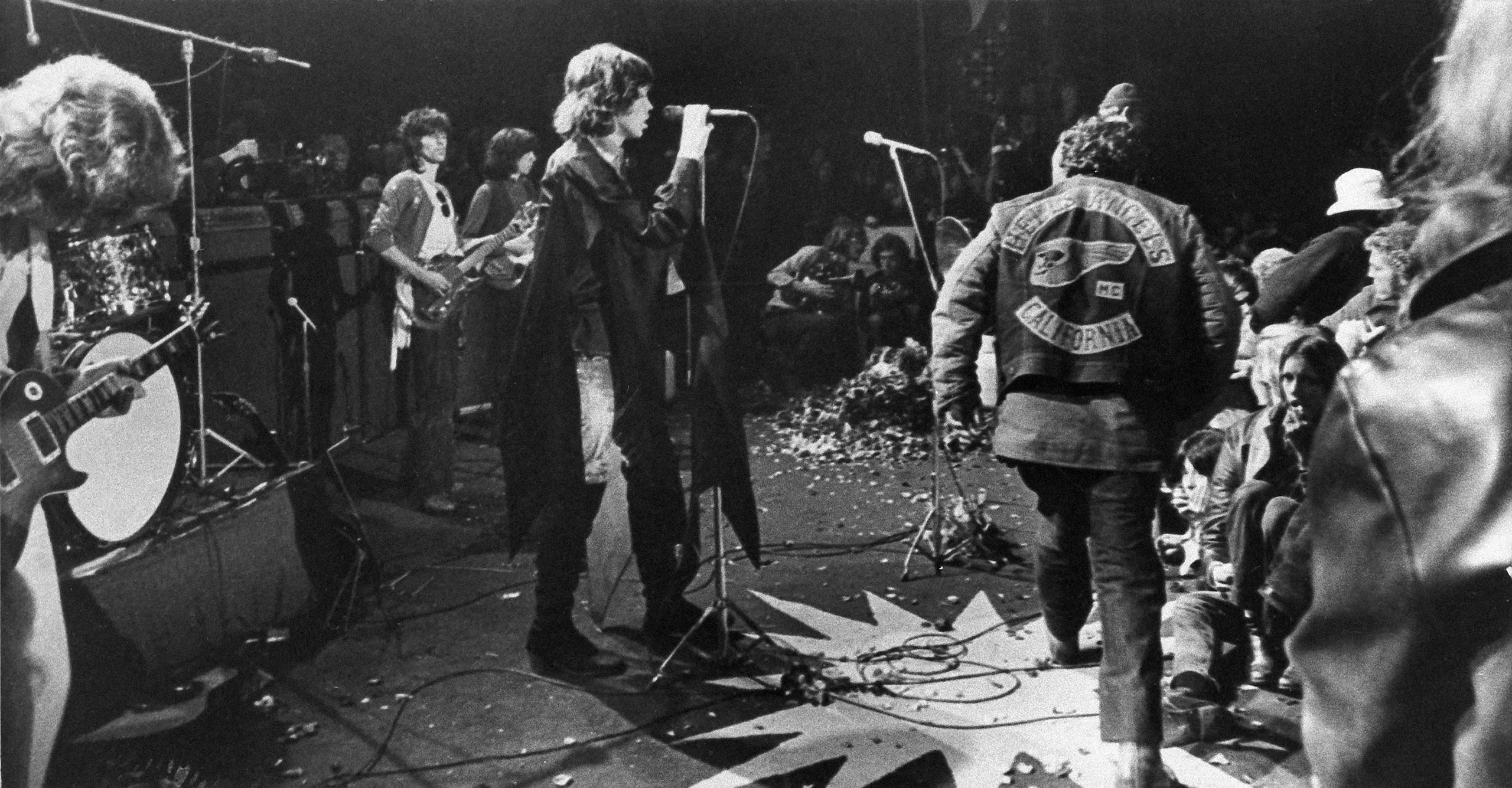 Mick Jagger sings at the Altamont Rock Festival at Livermore, Calif. on Dec. 6, 1969 while Hells Angels the cross stage during a melee.