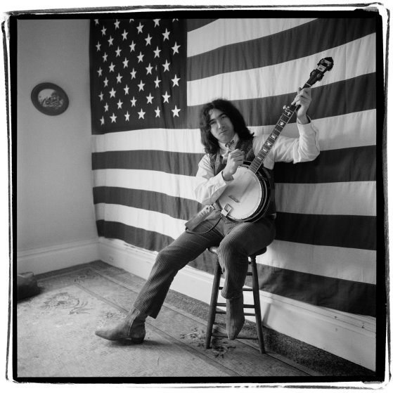 Jerry Garcia posing with banjo in front of American Flag, 1966.