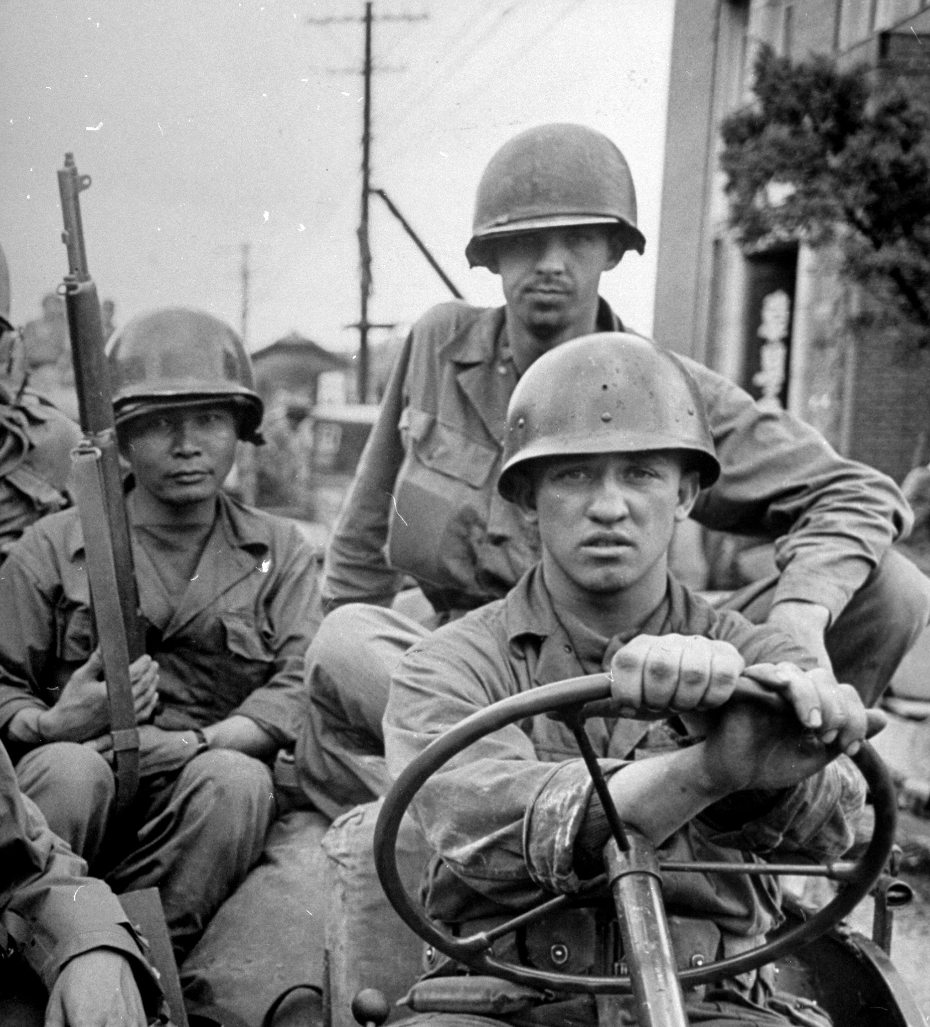 """<b>Caption from LIFE.</b> First U.S. infantry outfit to shed blood in the Korean war was the 24th """"Victory"""" Division, three of whose men are shown aboard a jeep in Korea. (This image was the cover of LIFE on July 31, 1950.)"""