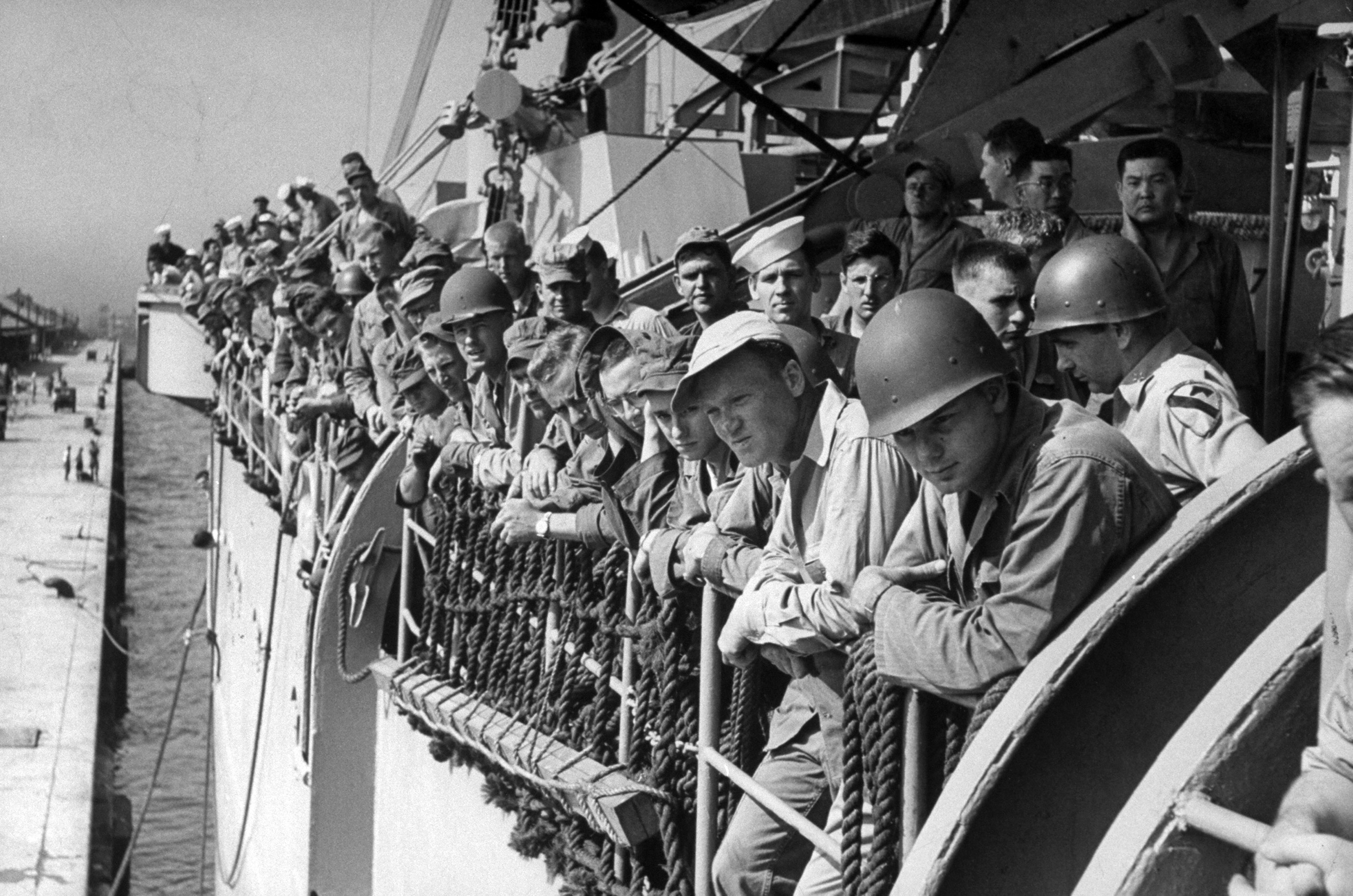 <b>Caption from LIFE.</b> Leaving Japan for unknown destination, soldiers of 1st Cavalry crowd transport's rail for last look at the dock.