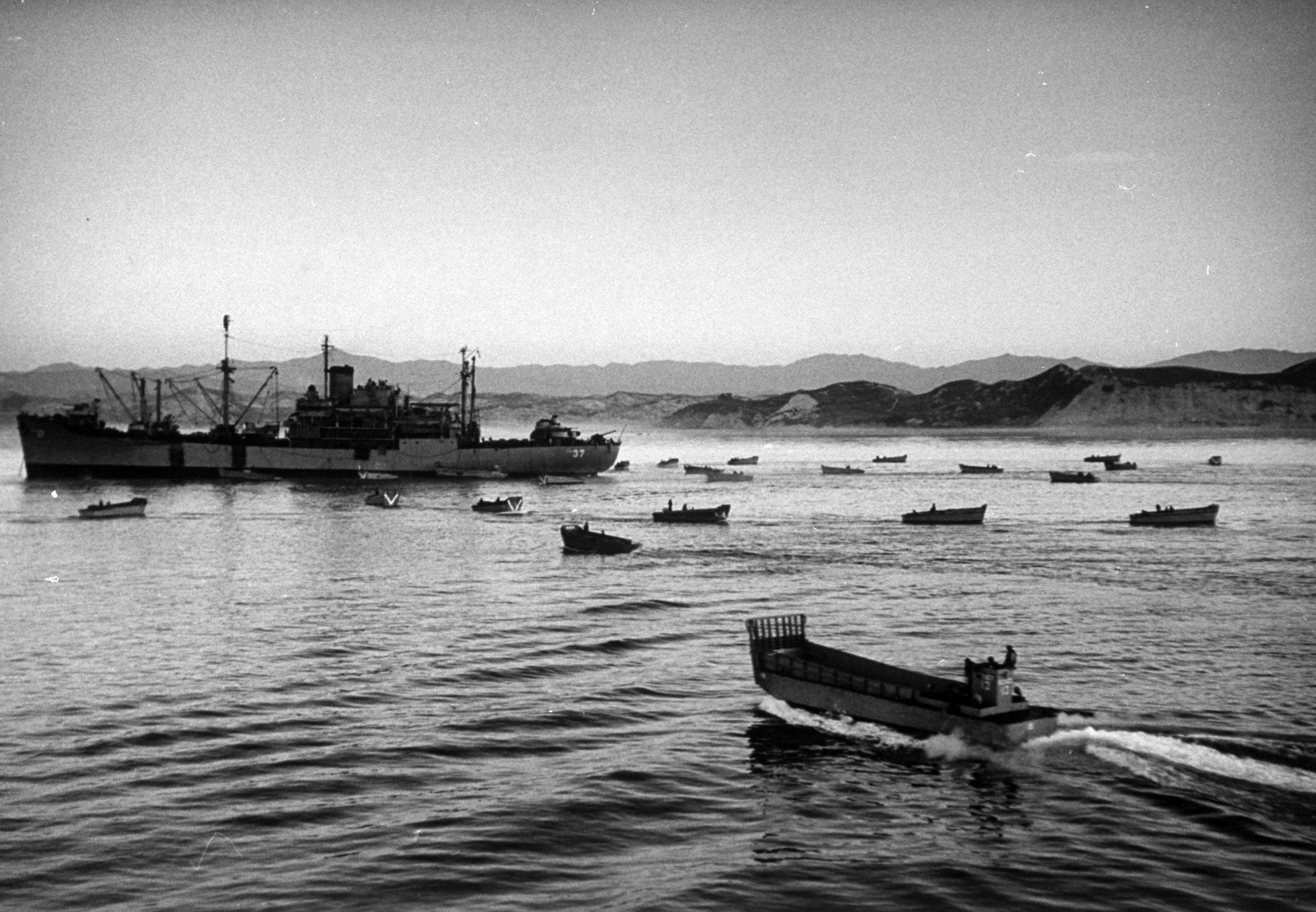 <b>Caption from LIFE.</b> At dawn on July 18 P'ohang-Dong's harbor is dotted with landing craft ready to take men ashore. A scouting party which went in earlier had already reported there was no opposition. This was the fastest amphibious landing in history. It was planned and staged in 10 days.