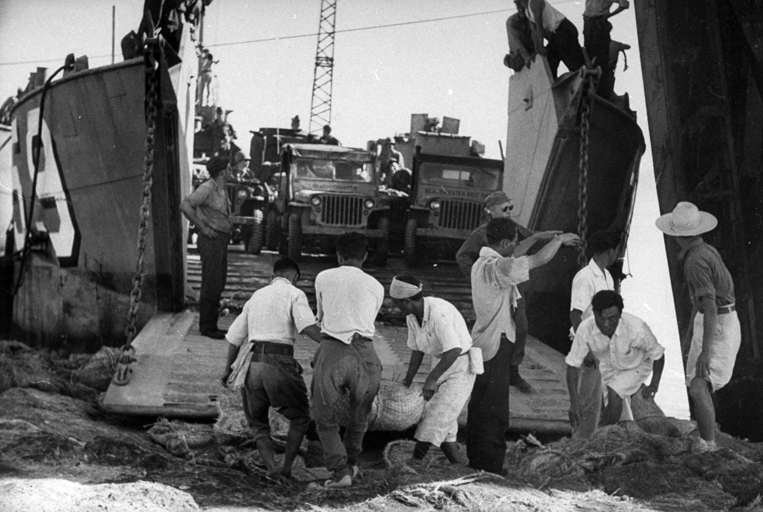 <b>Caption from LIFE.</b> Jeeps are unloaded from LCT with help of Koreans. They also helped build airbase near P'ohang-dong where fighters operated even before the landing.
