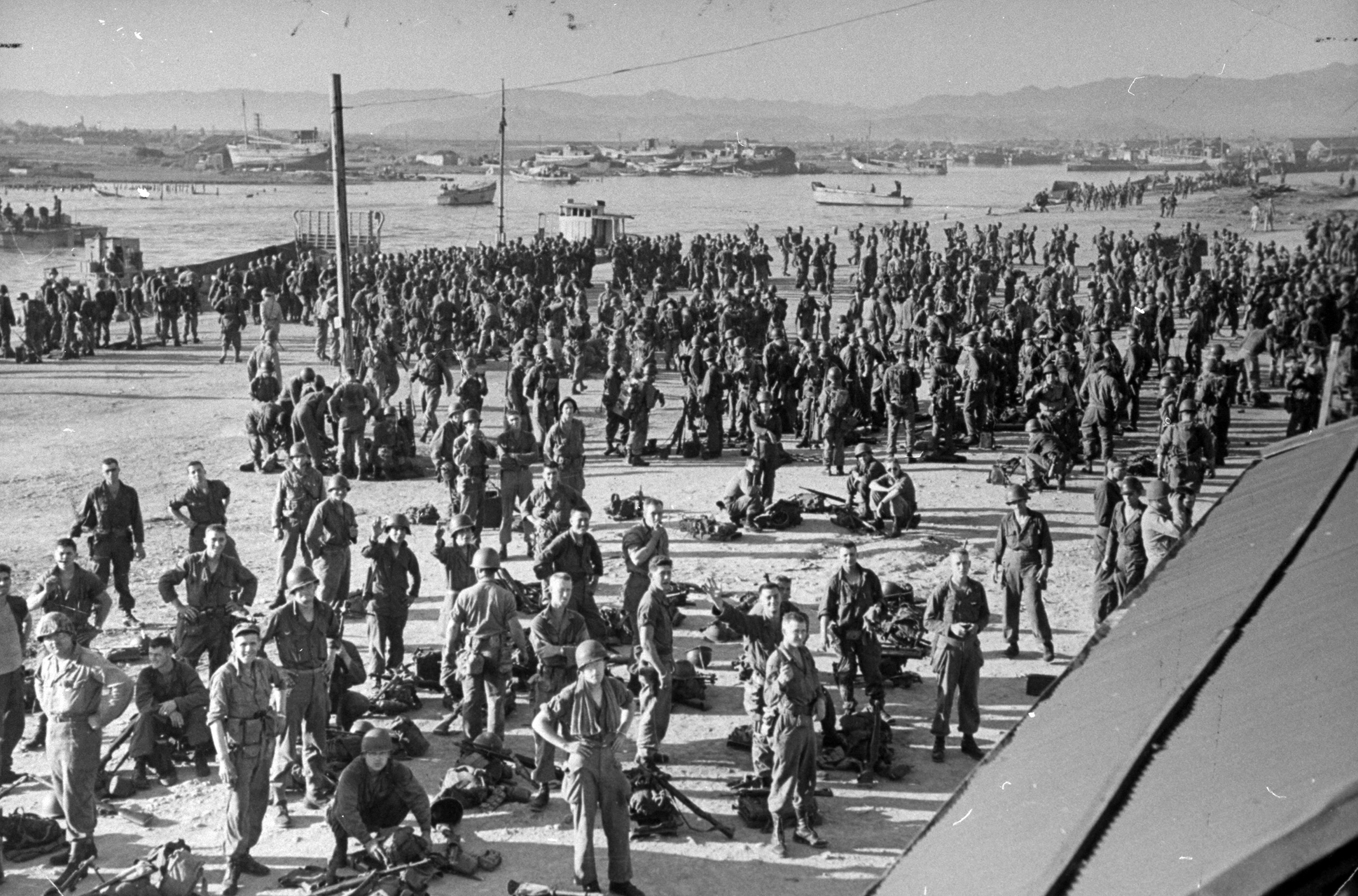 Newly arrived troops gathering at the beach awaiting orders to move further inland.