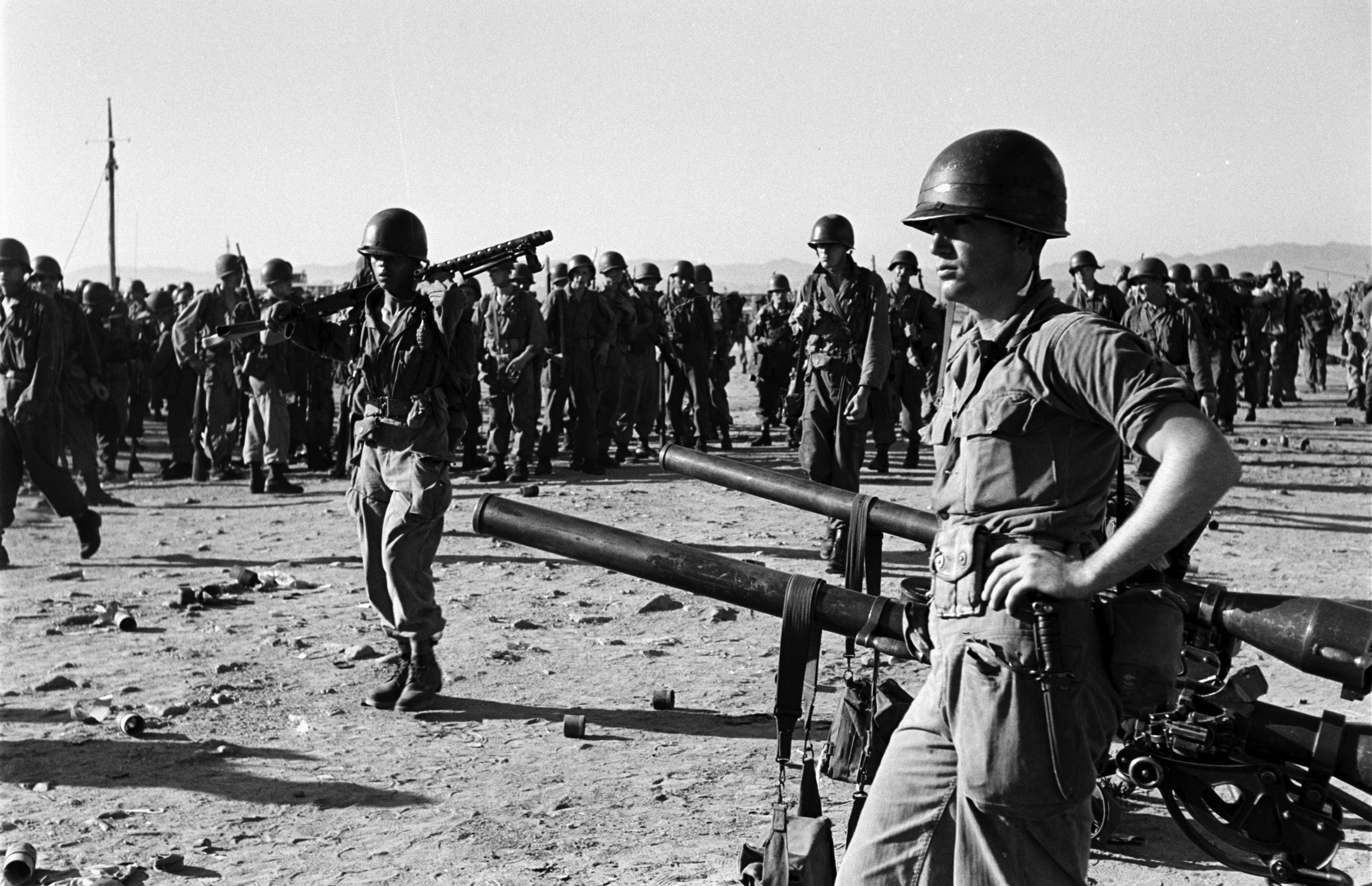 <b>Caption from LIFE.</b> Grim GI stands by tank-busting 75-mm, recoilless rifles as men and equipment build up on beach.