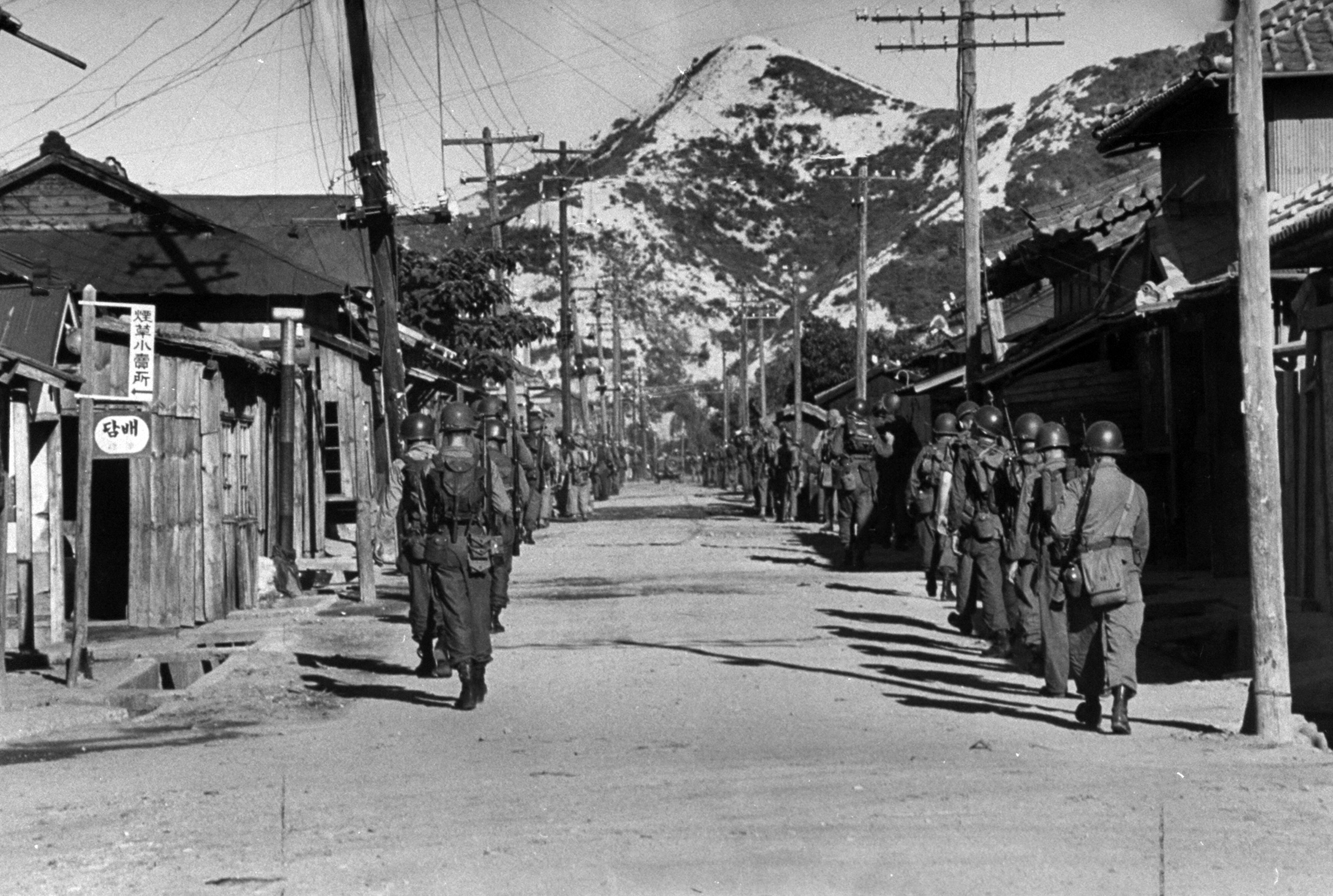 <b>Caption from LIFE.</b> GI's march through town to take positions in hills. A few Koreans stared from windows.