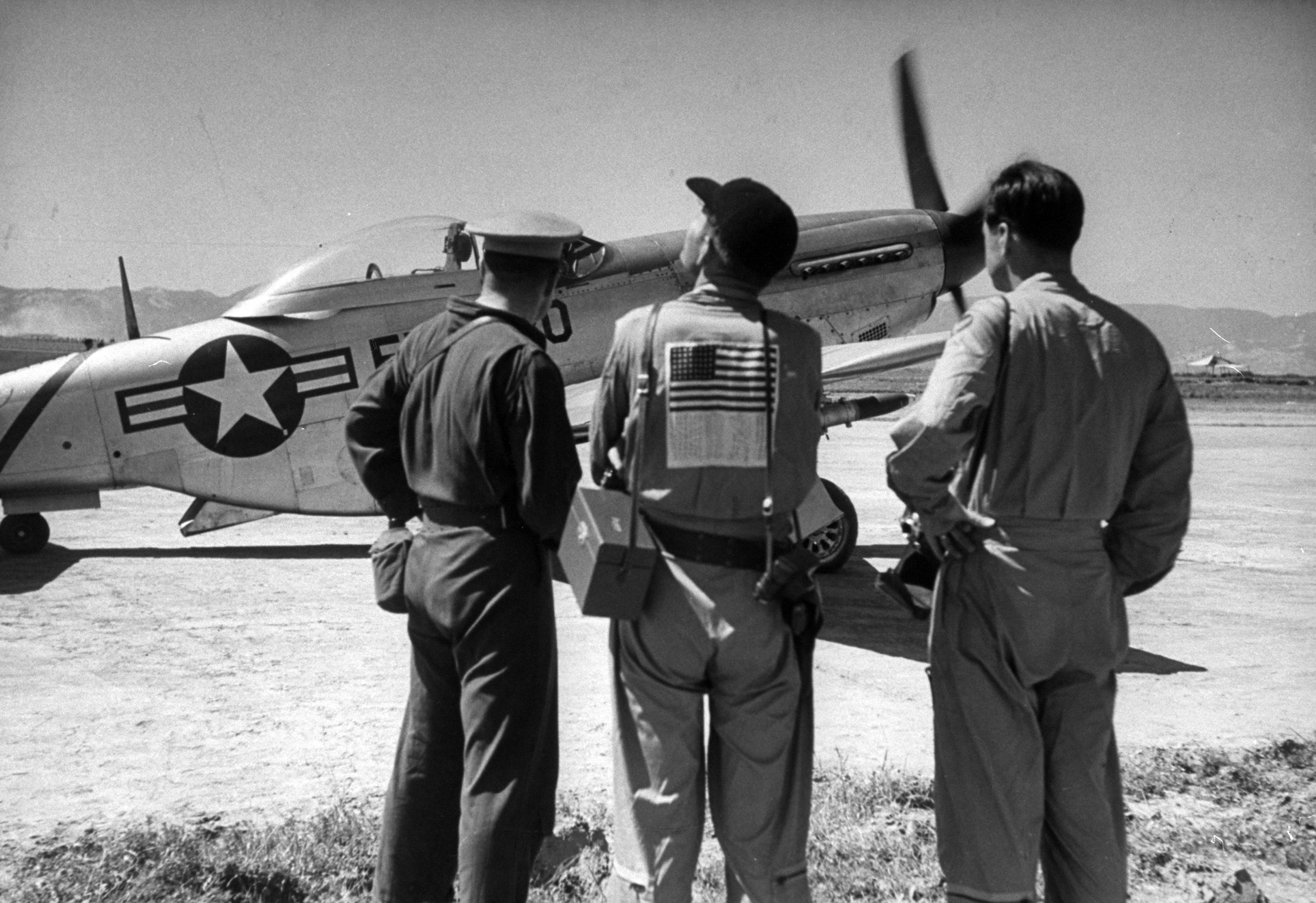 <b>Caption from LIFE.</b> Indentification is worn by U.S. flyer at base. Sign, in Korean, asks help should he be shot down.