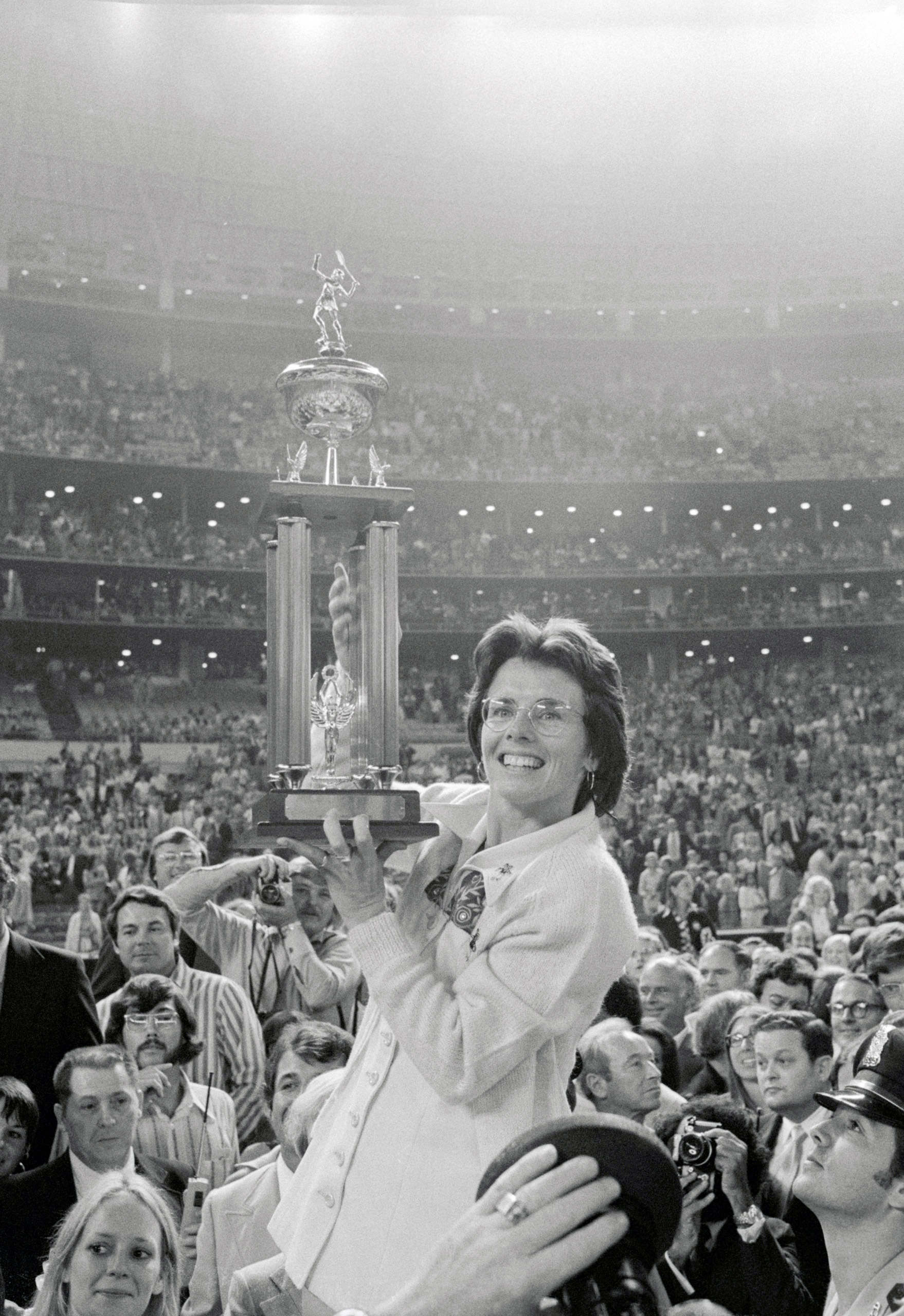 Pro tennis player Billie Jean King holds her newly won trophy high after beating Bobby Riggs in their $100,000 winner-take-all  Battle of the Sexes  tennis match on September 20, 1973.  [The] conventional wisdom [was] that an adequate male player should be able to beat a first-class woman,  TIME commented.  Almost everyone was wrong.