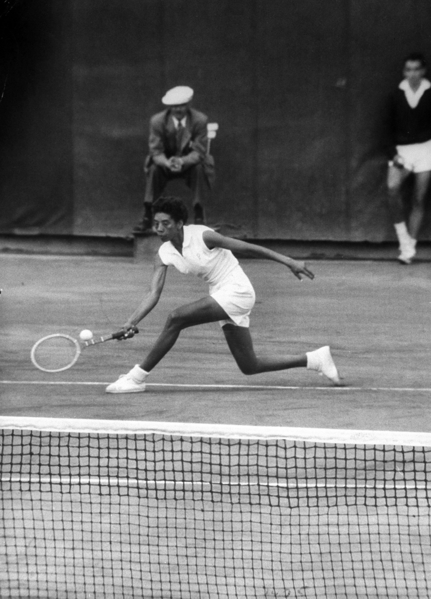 Caption from LIFE. Range and reach enable 5-foot 10 1/2 inch Althea to return well-placed shot in French championship. Though not a first-class strategist, she has learned how to follow up her shots. Once content to rely entirely on her extraordinary power and big service, she has now developed a steady backhand and a sharp volley.