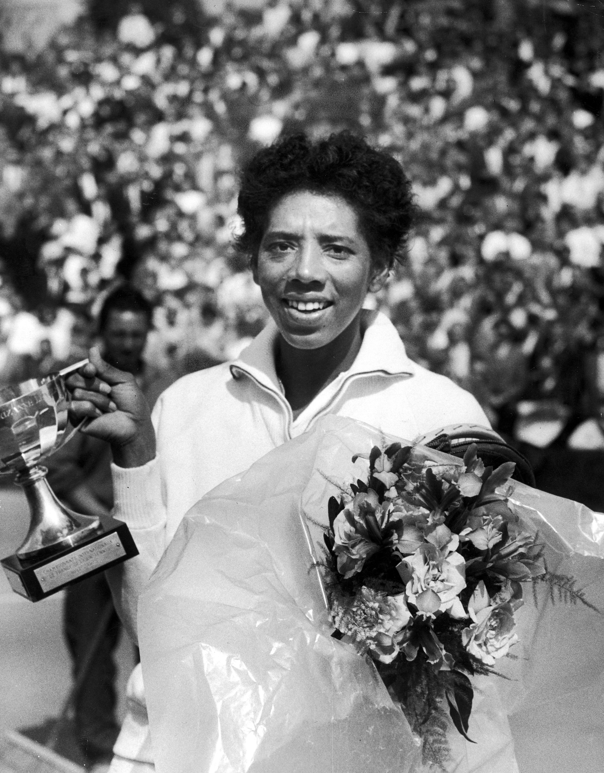 Caption from LIFE. Most prized trophy, the Suzanne Lenglen Cup, is held by Althea after winning French title.