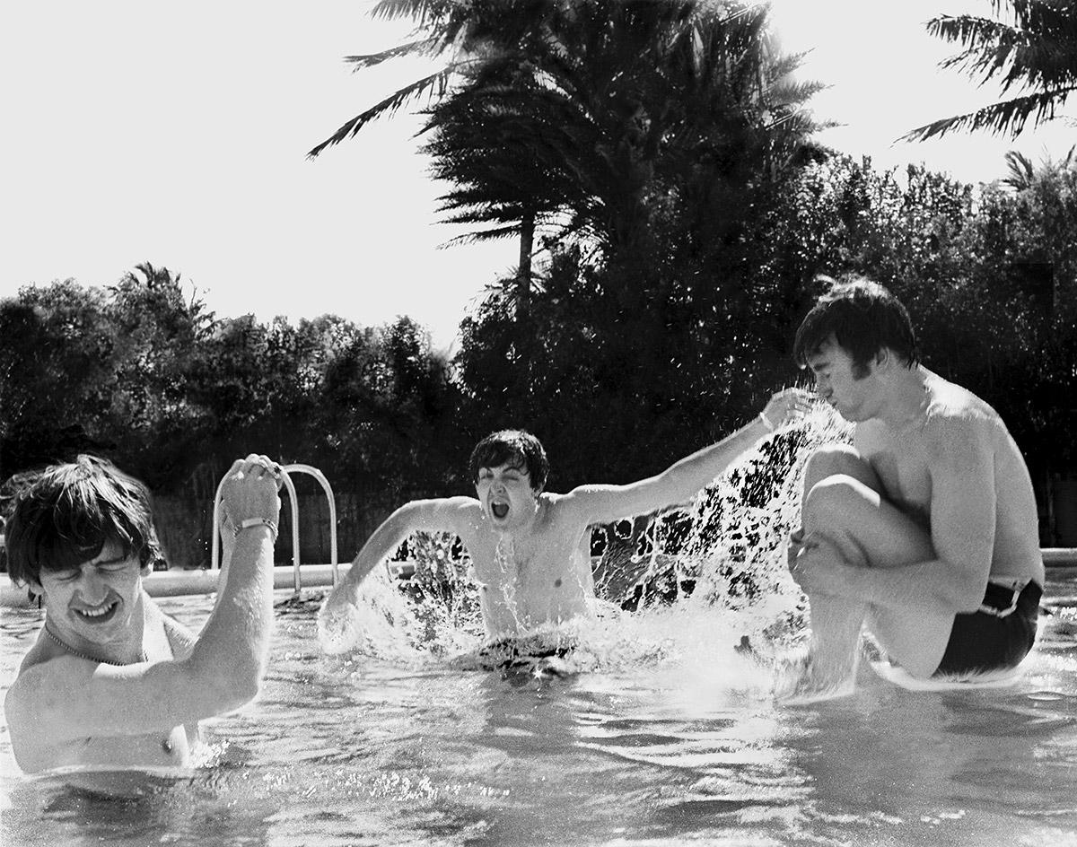 John Lennon doing cannonballs, Paul McCartney splashing and Ringo Starr turning away in Miami, 1964.