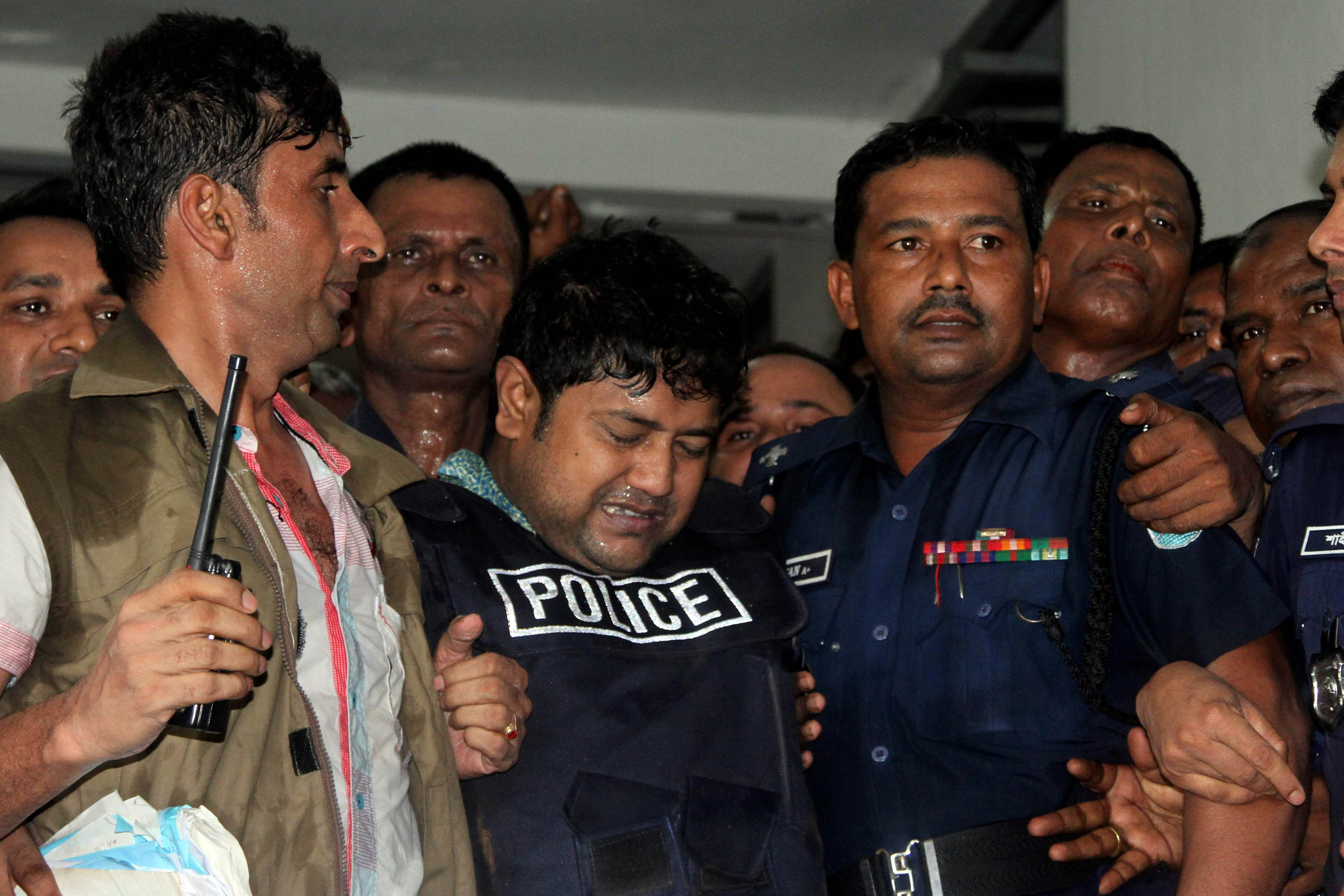 Bangladeshi property tycoon Sohel Rana (C), seen wearing police-issue body armor, is escorted for his appearance in court in Dhaka on April 29, 2013.