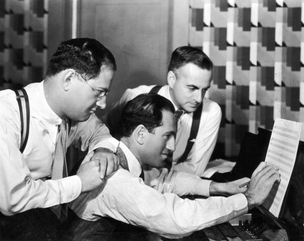 Circa 1925: George Gershwin (1888 - 1937) (C) at work as his brother and songwriting partner, lyricist Ira Gershwin (1896 -1983) (L), and British dramatist Guy Bolton (1884 - 1979), look on.