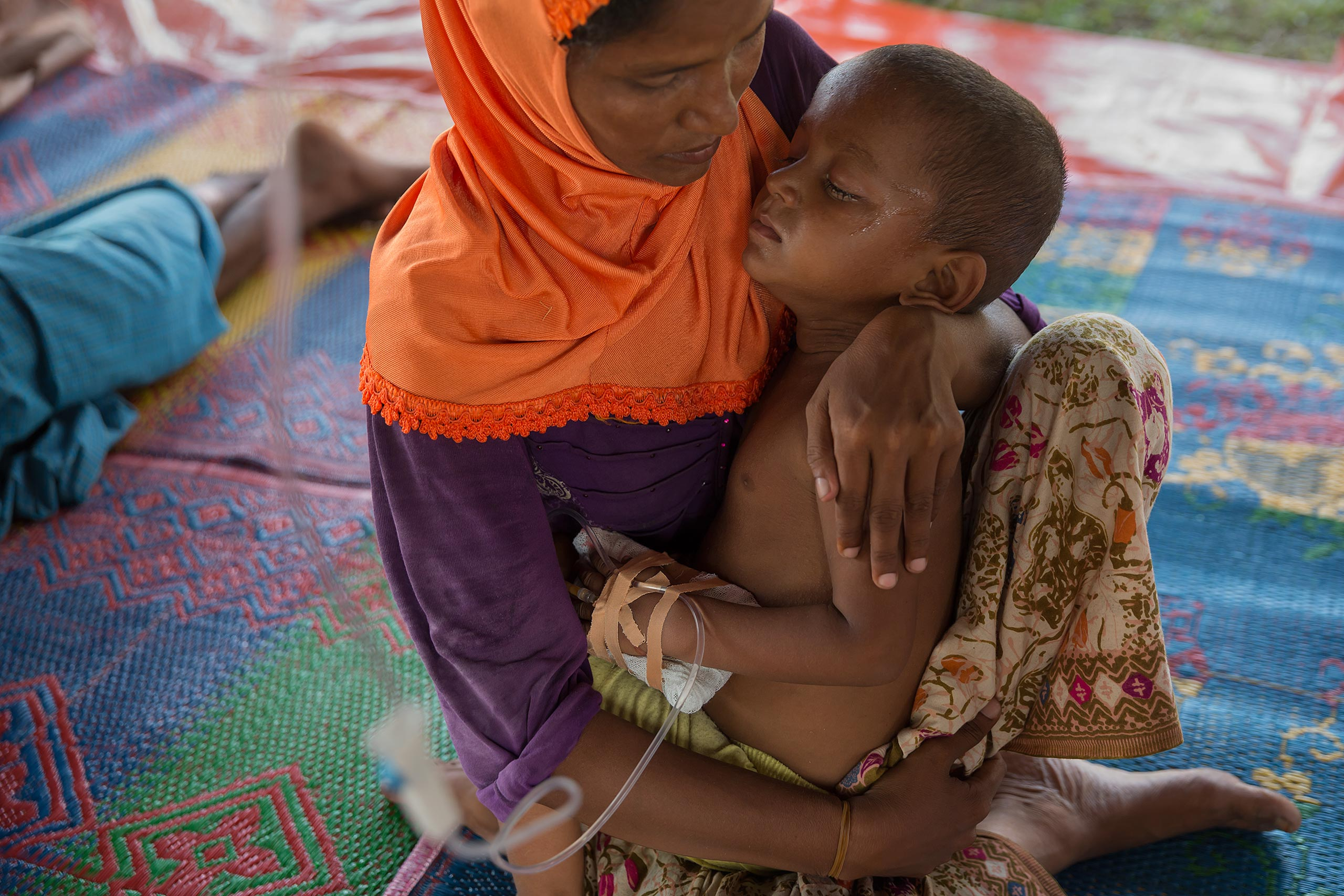 A mother holds her child at a refugee camp in Bayeun, outside of Langsa, Indonesia, where they were given shelter, food and medical care by Indonesian and international NGOs.