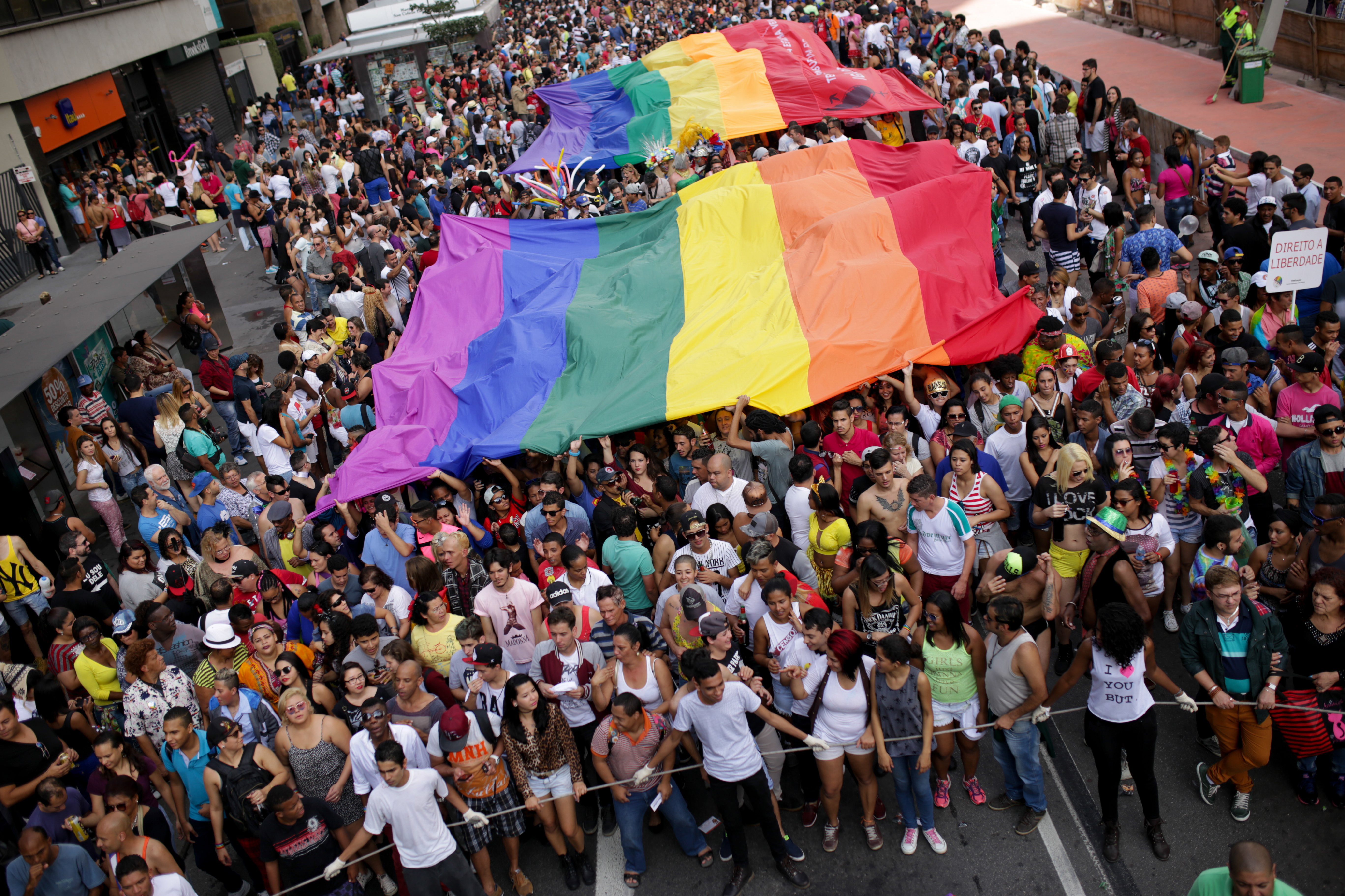 Participants of Sao Paulo's 19th annual Gay Pride Parade hold a large flag with the LGBT colors in Sao Paulo on June 7, 2015.