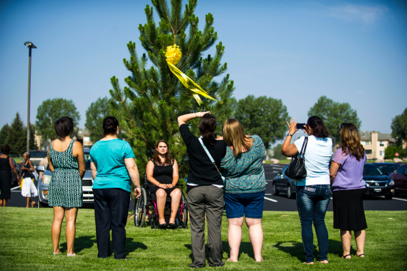 Ashley Moser poses for a picture in front of a tree bearing a ribbon for her 6-year-old daughter Veronica Moser-Sullivan, who was killed in the attack on the Century Aurora 16 movie theater in Aurora, Colo., on July 20, 2014