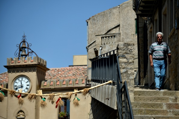 A man walks in the center of the village of Gangi, 120 kms from Palermo, on August 14, 2014