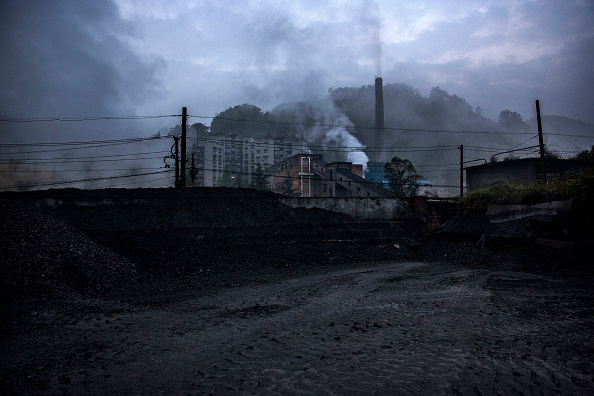 Coal to be used by coal powered steam engines is seen backdropped by a coal fired power plant on March 27, 2015 at a station near the town of Shixi , Sichuan Province, in Southern China