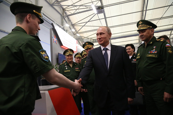 Russian President Vladimir Putin shakes hands with an officer as Defence Minister Sergei Shoigu looks on during his visit to the International Military-Technical Forum  ARMY-2015  at Patriot park June 16, 2015 in Kubinka, Russia