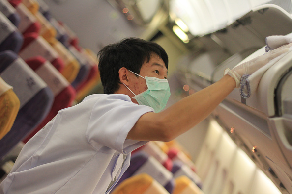 Thai Airways (THAI)  implements preventive measures regarding the MERS virus on THAI flights within  affected areas; Thai officers spray disinfectant on passenger seats aboard a Thai Airways Airbus A330-300 at Suvarnabhumi airport in Bangkok