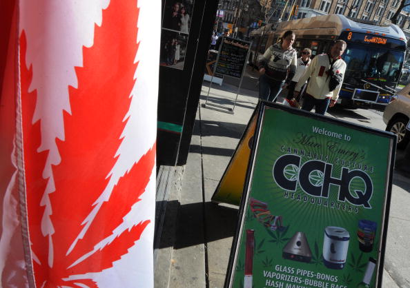 Visitors walk past a flag similiar to the Canadian one but showing a cannabis plant instead of a maple leaf at a store in Eastside Vancouver during the Vancouver Winter Olympics on February 22, 2010