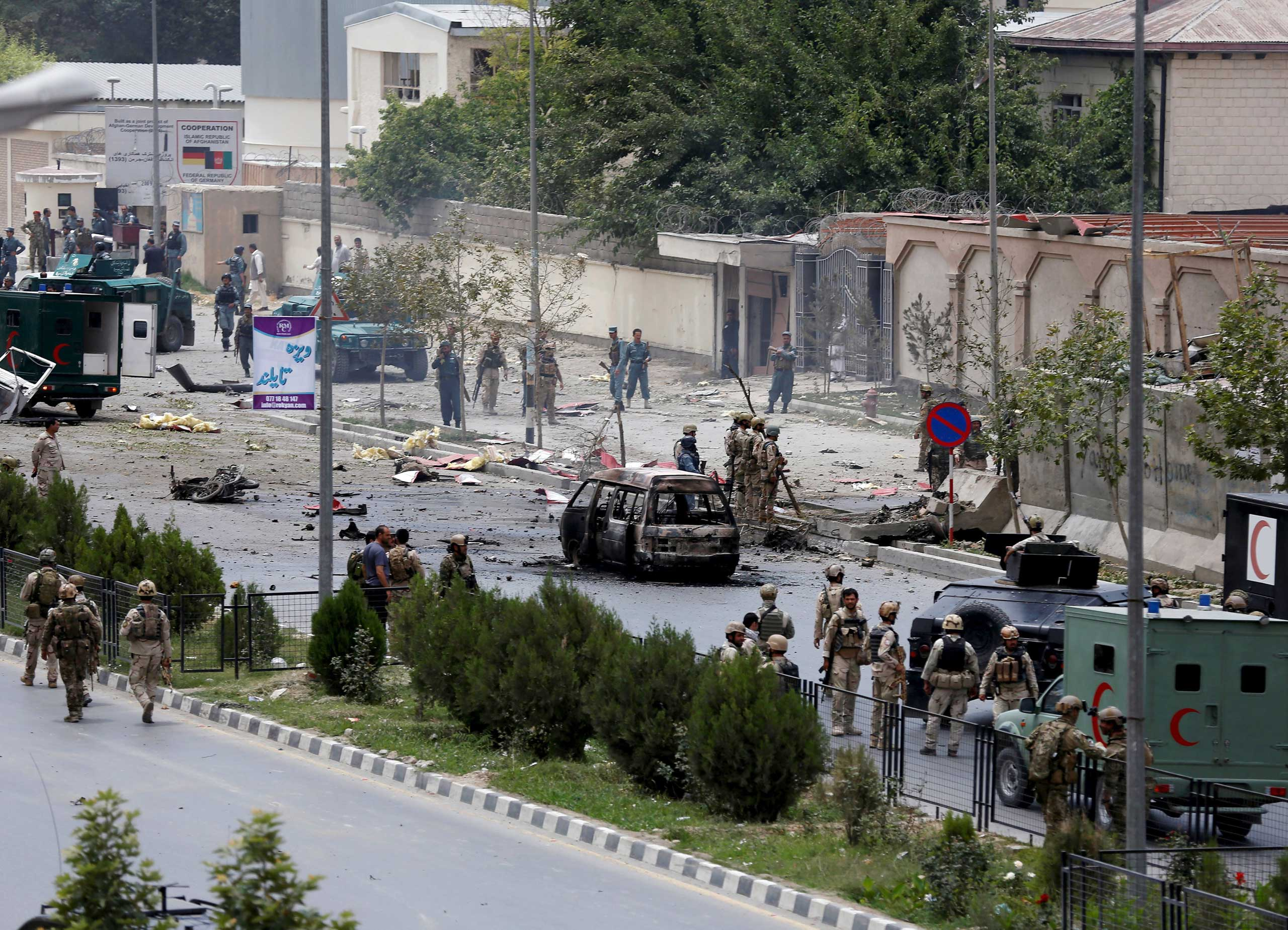Members of security forces and police officers stand at the site of a suicide bomb attack near the Afghan Parliament in Kabul, Afghanistan on June 22, 2015.