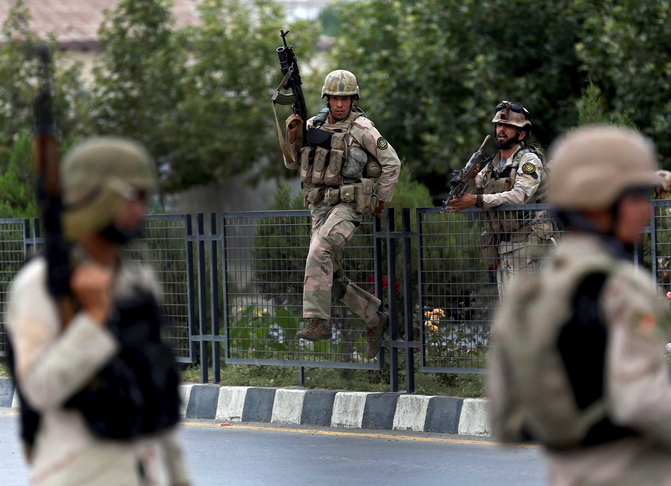 Members of Afghan security forces climb over a fence as they arrive at the site of an attack near the Afghan Parliament in Kabul, Afghanistan on June 22, 2015.
