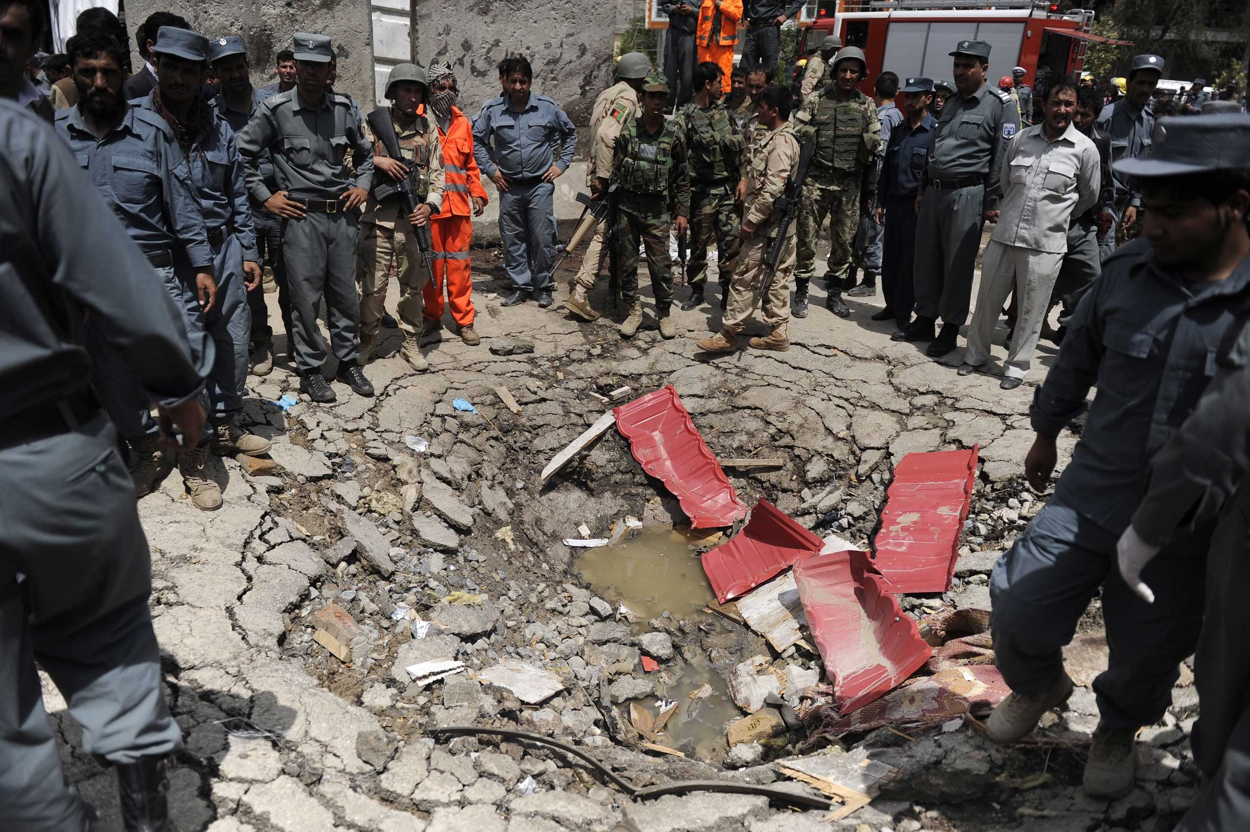 Afghan security officials stand beside a crater that was formed at the scene of a suicide bomb attack outside  the Afghan Parliament, in Kabul, Afghanistan, on June 22, 2015.
