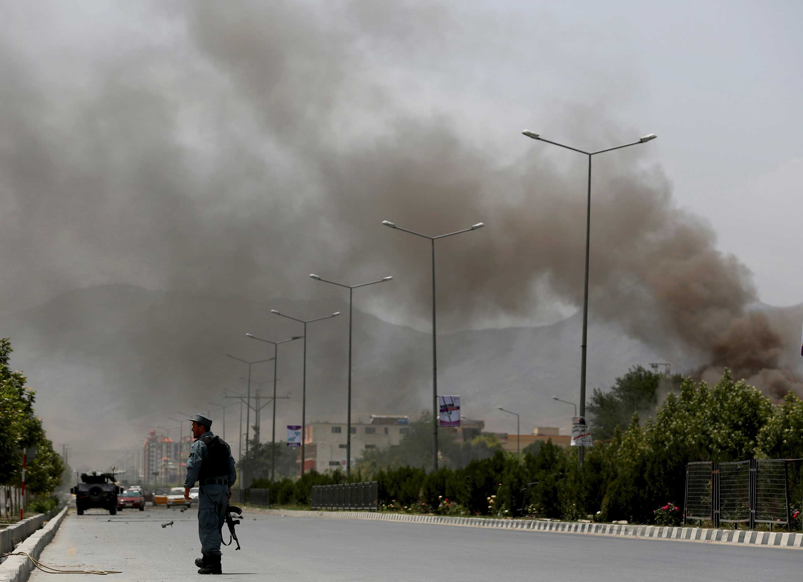A policeman stands close to the site of an attack as smoke billows in the sky, near the Afghan Parliament in Kabul, Afghanistan on June 22, 2015.