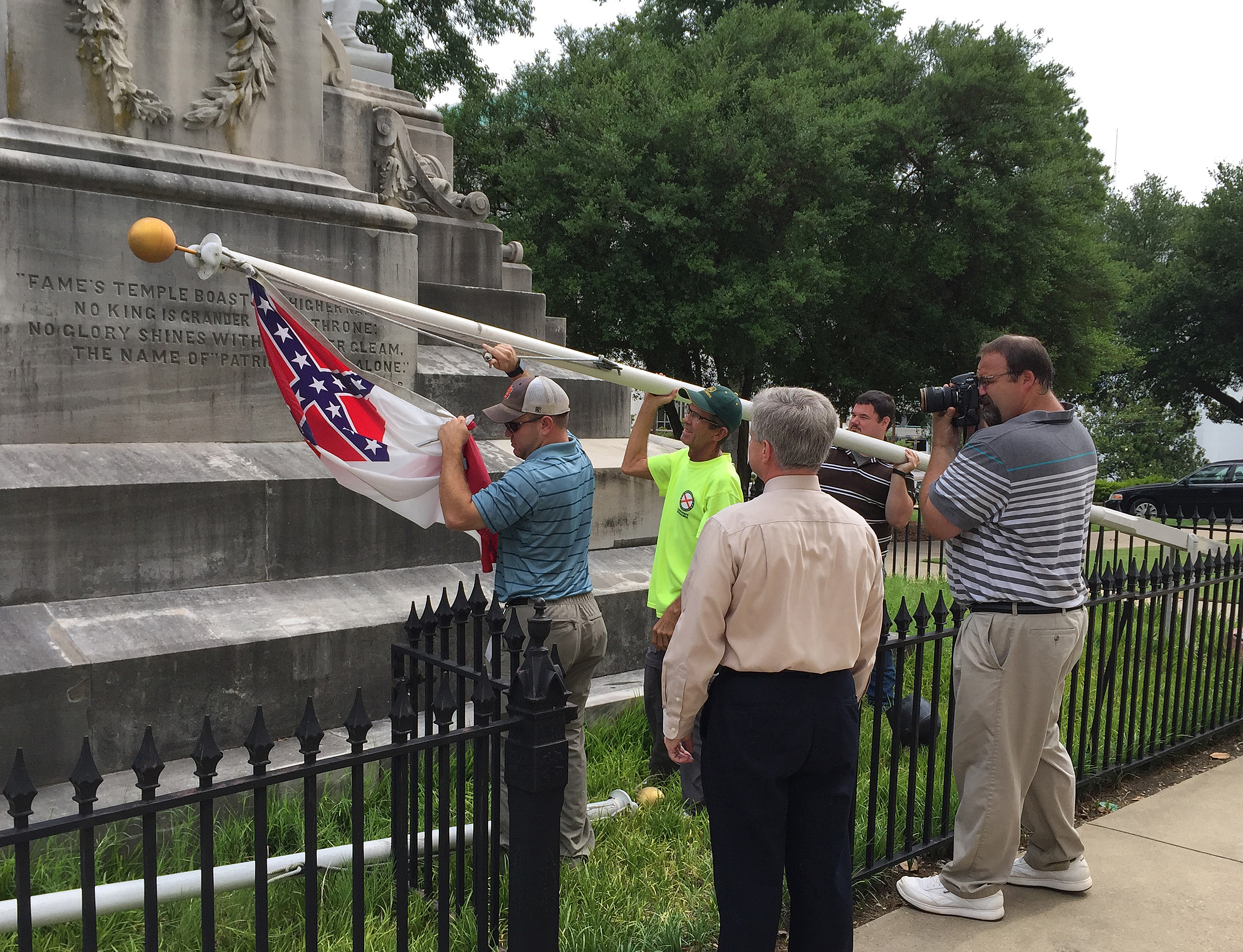 State workers take down a Confederate national flag on the grounds of the state Capitol, June 24, 2015, in Montgomery, Ala.