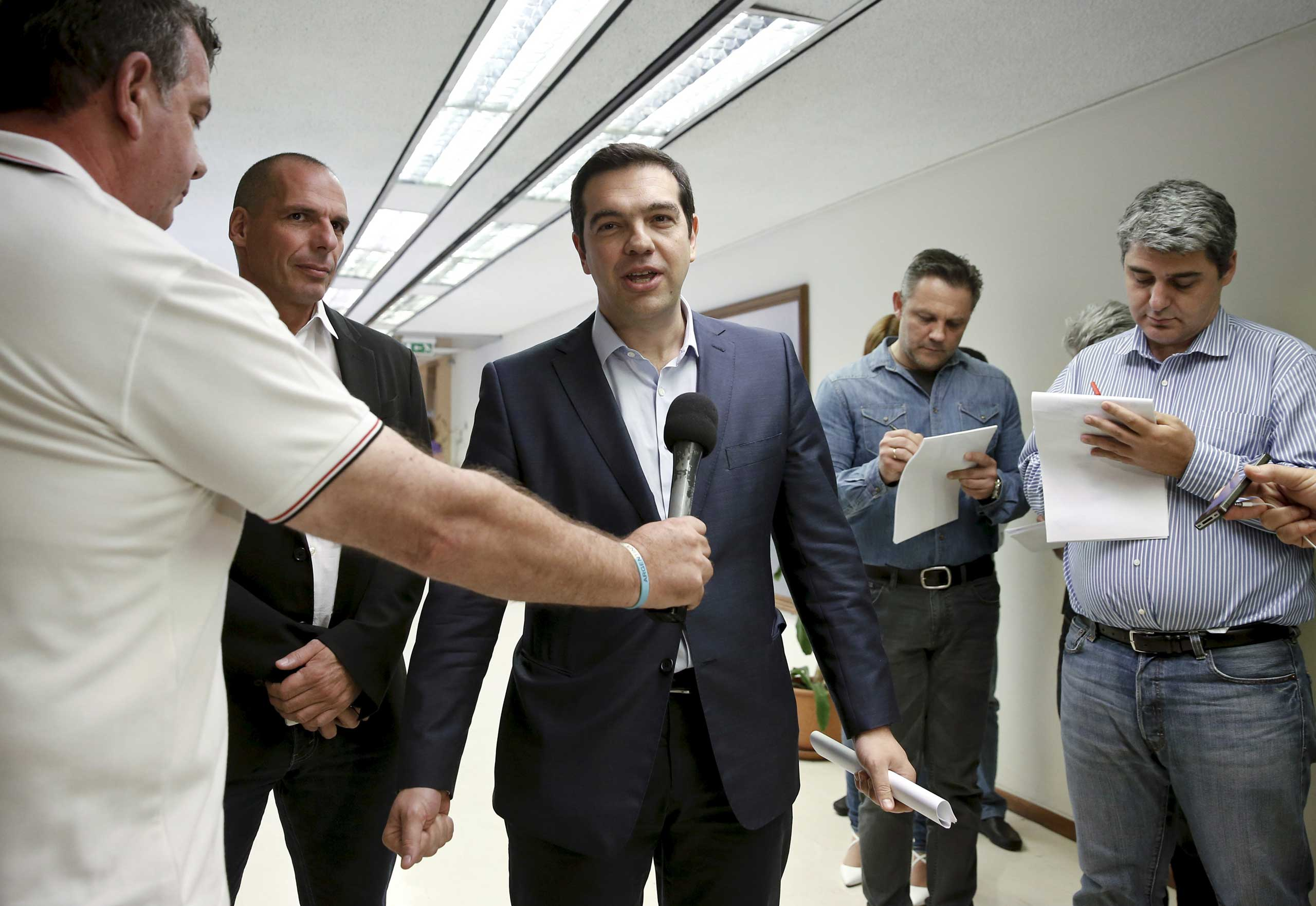 Greek Prime Minister Alexis Tsipras (C) makes statements to the media as Finance Minister Yanis Varoufakis (2nd L) looks on after a meeting at the ministry in Athens May 27, 2015.