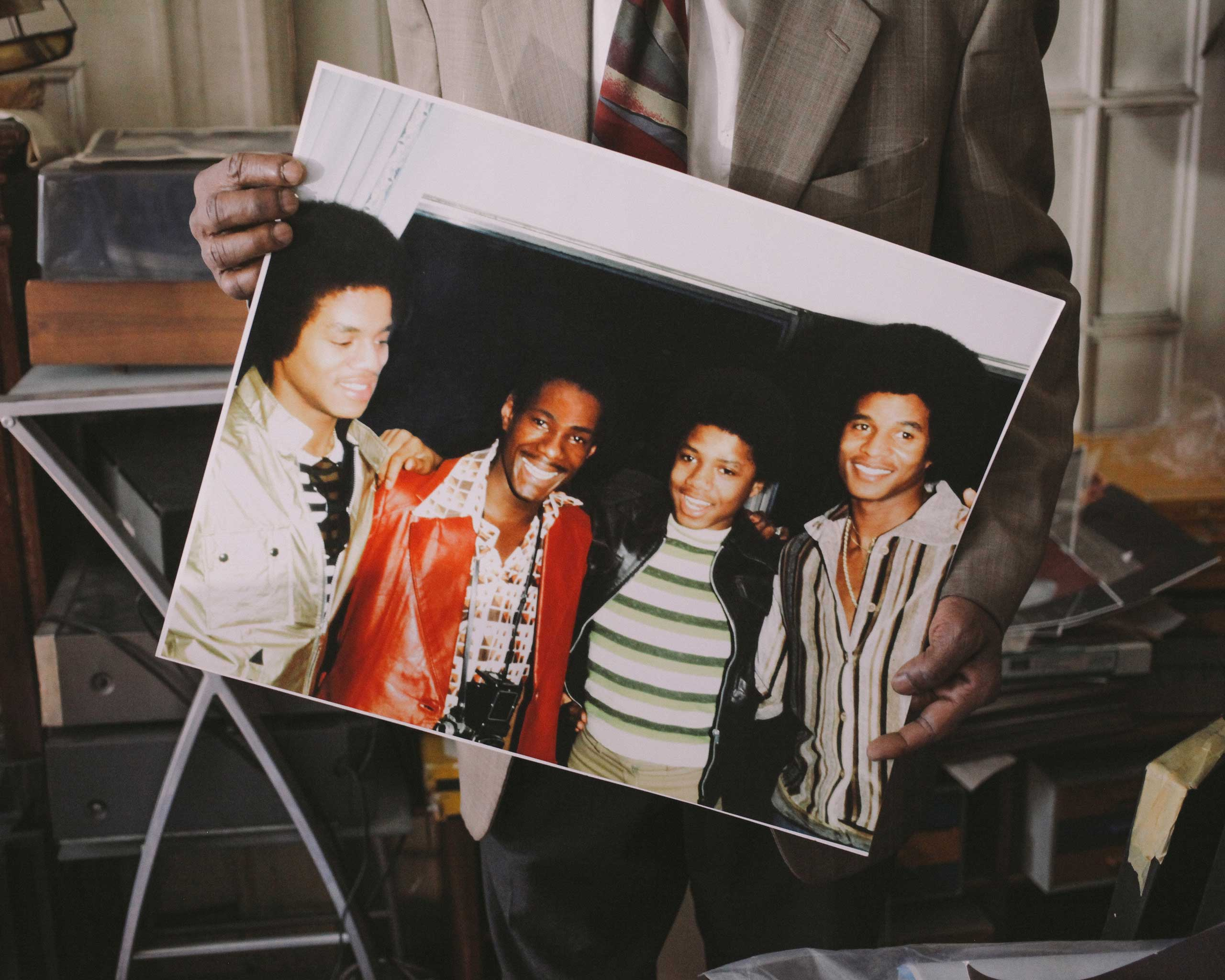 Alix Dejean holds a photo of himself with the Jacksons.