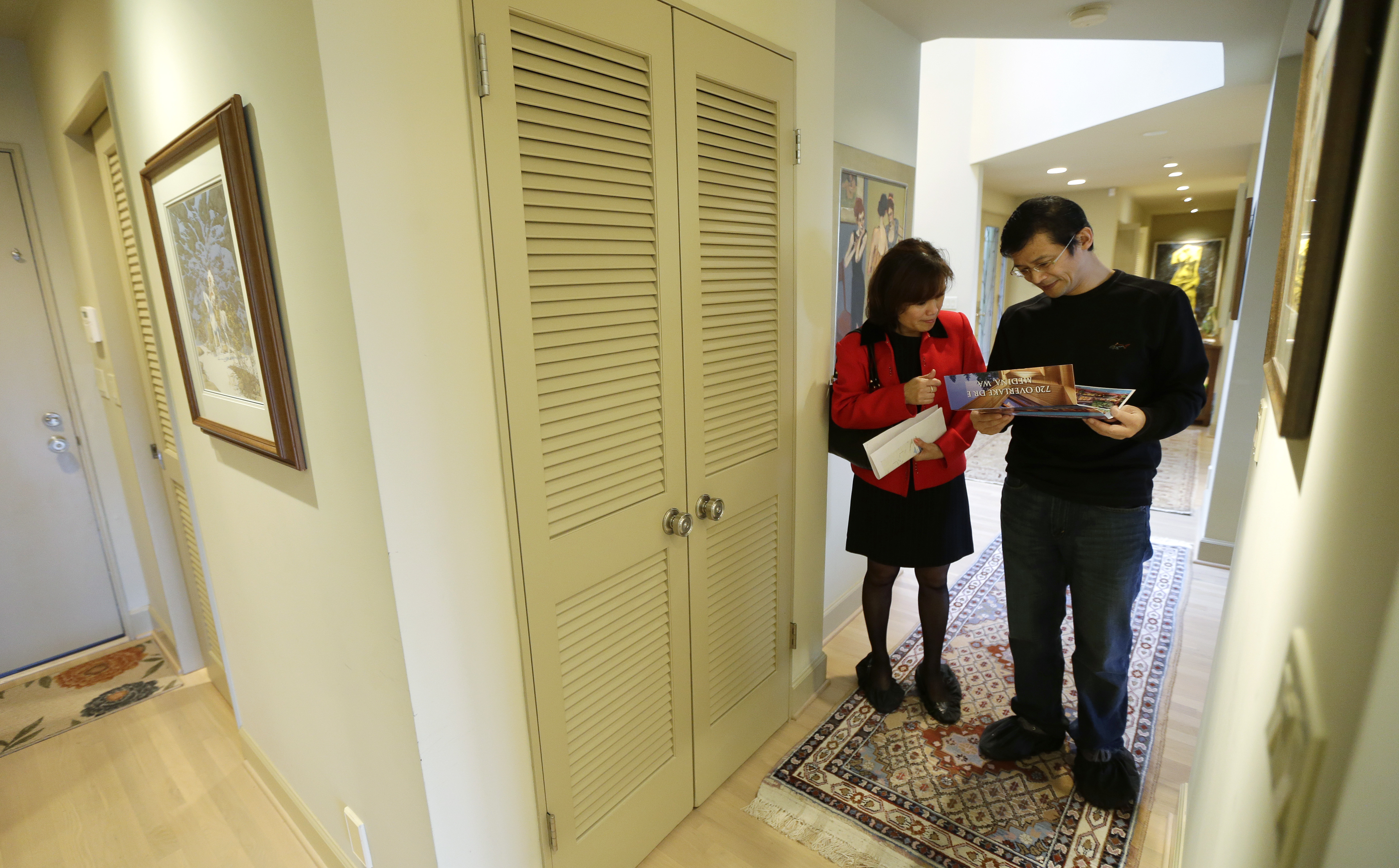 Janie Lee, left, a residential specialist with John L. Scott Real Estate, shows a home for sale to her client, Hongbin Wei, of Beijing, China, Thursday, Dec. 18, 2014, in Medina, Wash., near Seattle