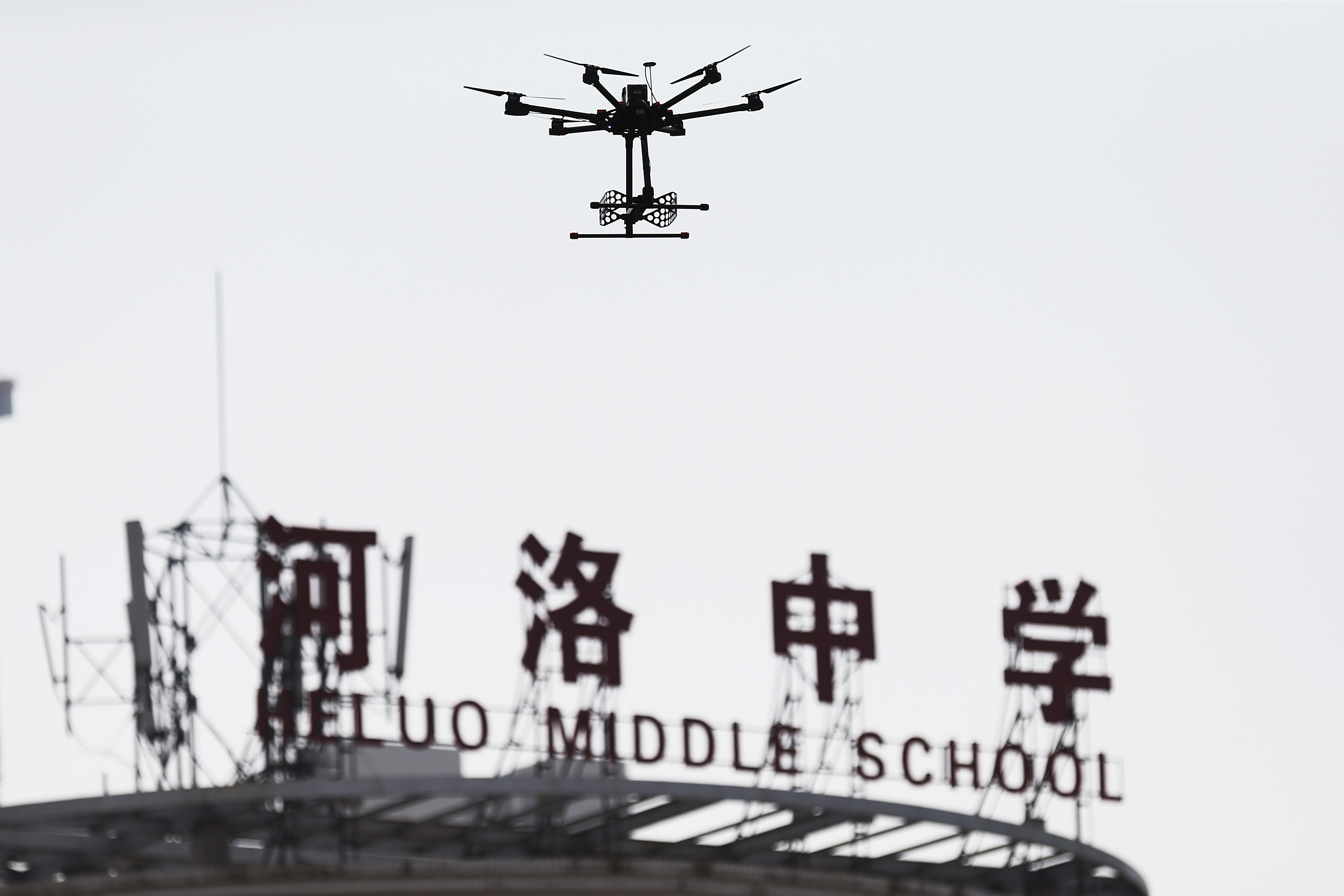 An unmanned aerial vehicle (UAV), or drone, used to detect radio signals to prevent student from cheating, hovers over an exam site during the first examination of the 2015 National College Entrance Exam, also known as Gaokao, at Heluo Middle School in Luoyang city, central China's Henan province, 7 June 2015.