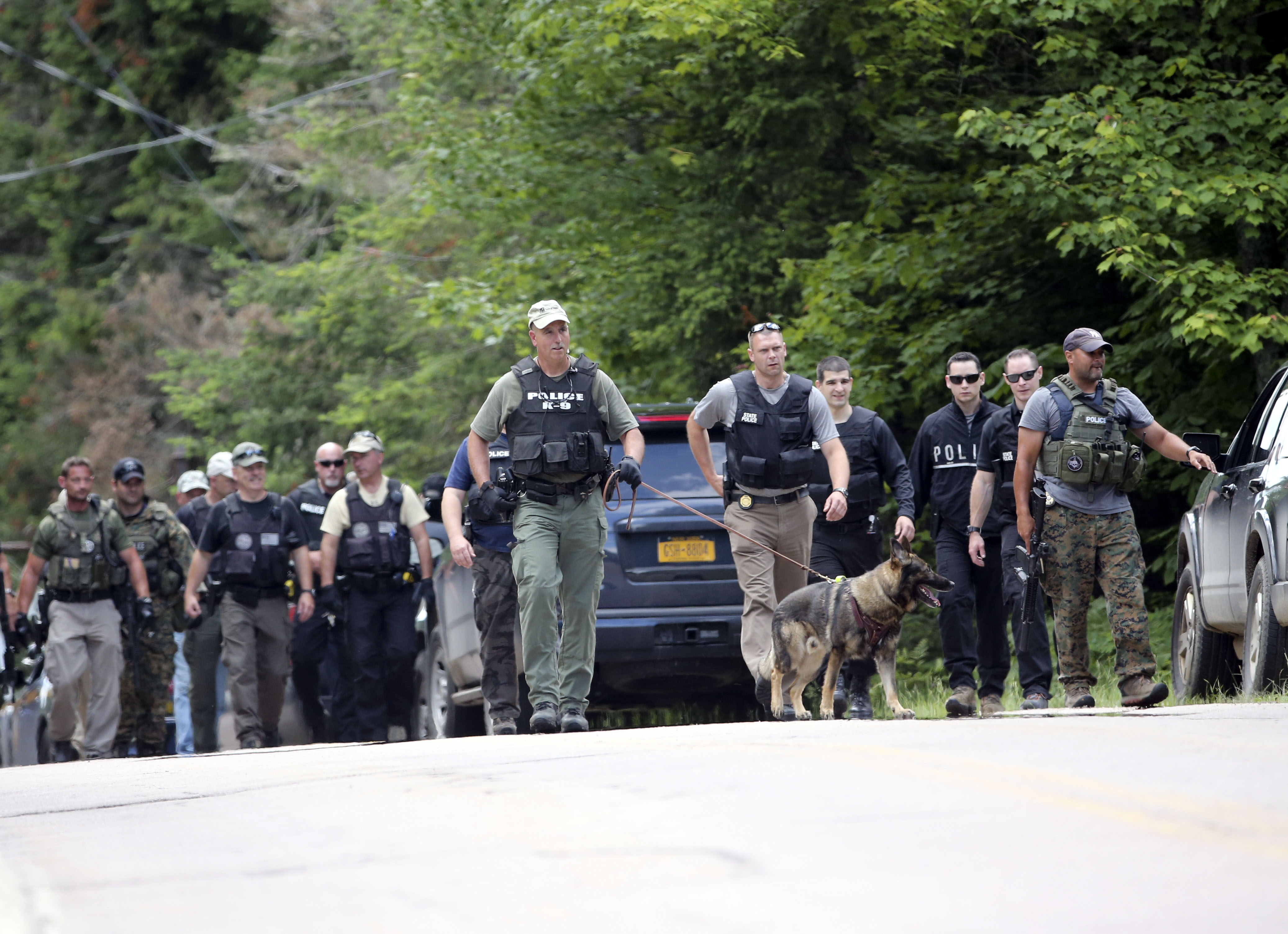 Law enforcement officers walk along a road as the search continues for two escaped prisoners from the Clinton Correctional Facility in Dannemora, on Monday, June 22, 2015