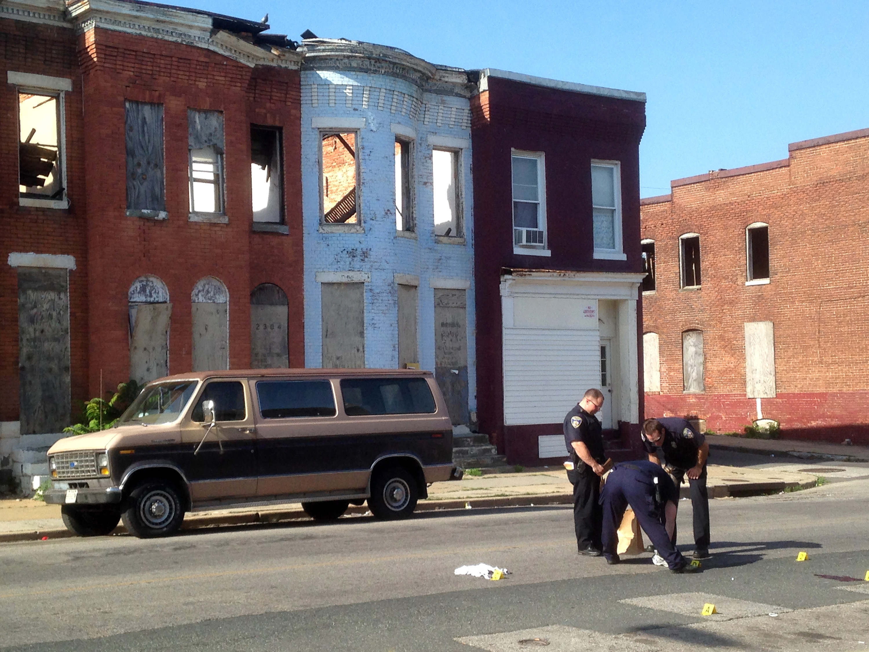 Police pick up a pair of tennis shoes after a double shooting in the 2300 block of E. Preston Street in Broadway East on May 24, 2015 in Baltimore, Md.