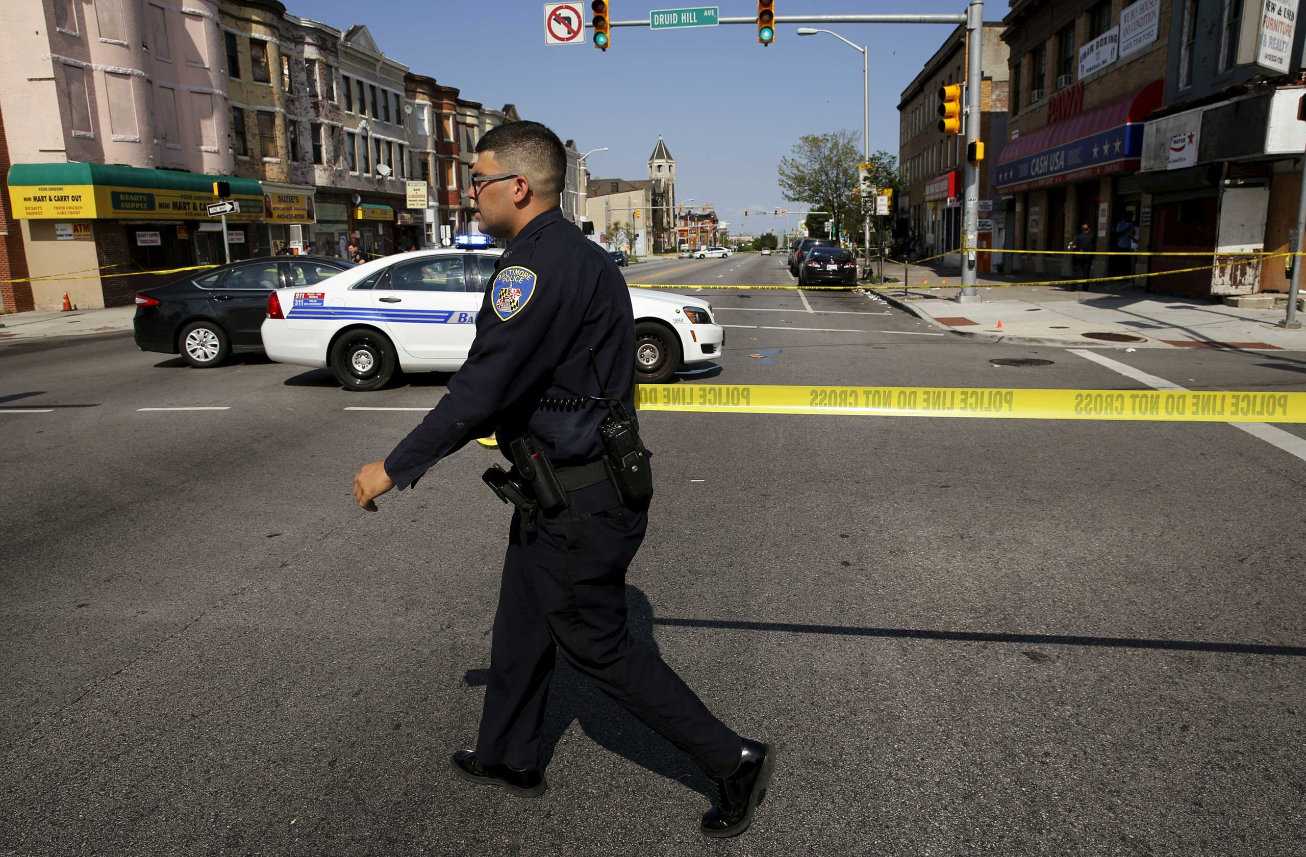 A Baltimore police officer attempts to secure a crime scene with tape at the scene of a shooting in West Baltimore on May 30, 2015.